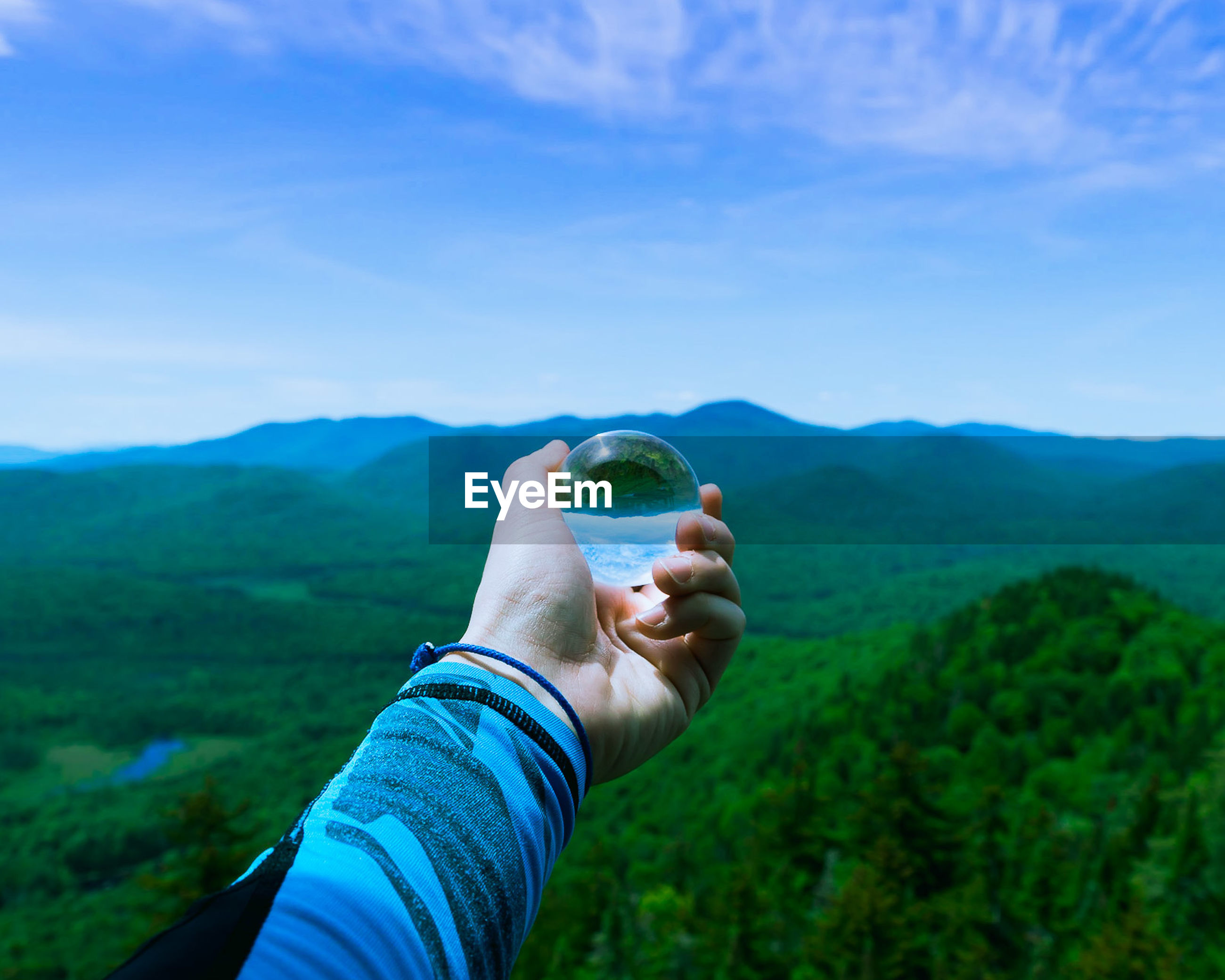 Cropped image of person holding crystal ball against mountains