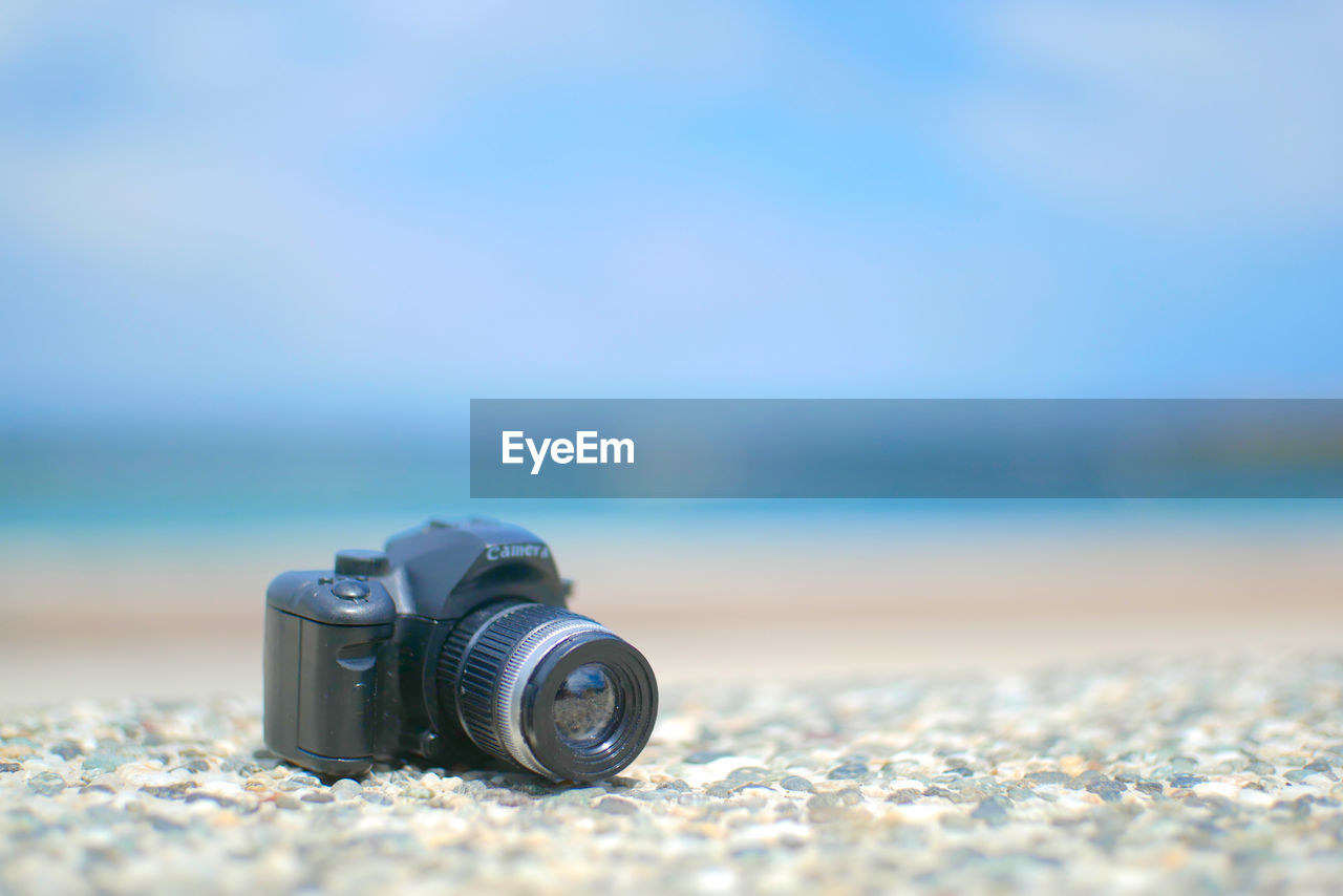 selective focus, land, photography themes, beach, day, no people, sea, camera - photographic equipment, technology, close-up, nature, focus on foreground, scenics - nature, blue, sky, water, sand, photographic equipment, outdoors, surface level, digital camera