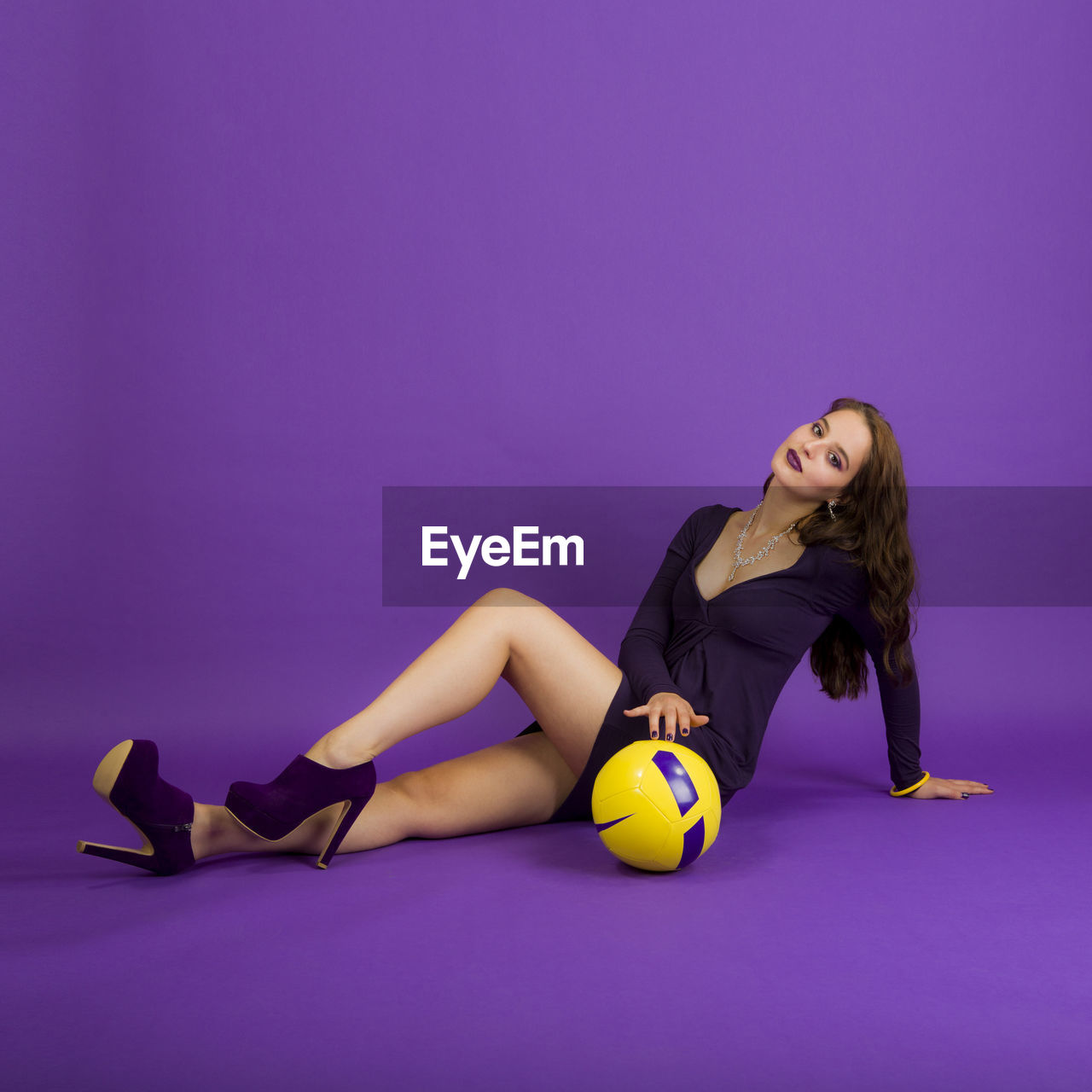 Portrait of young woman sitting with ball against purple background