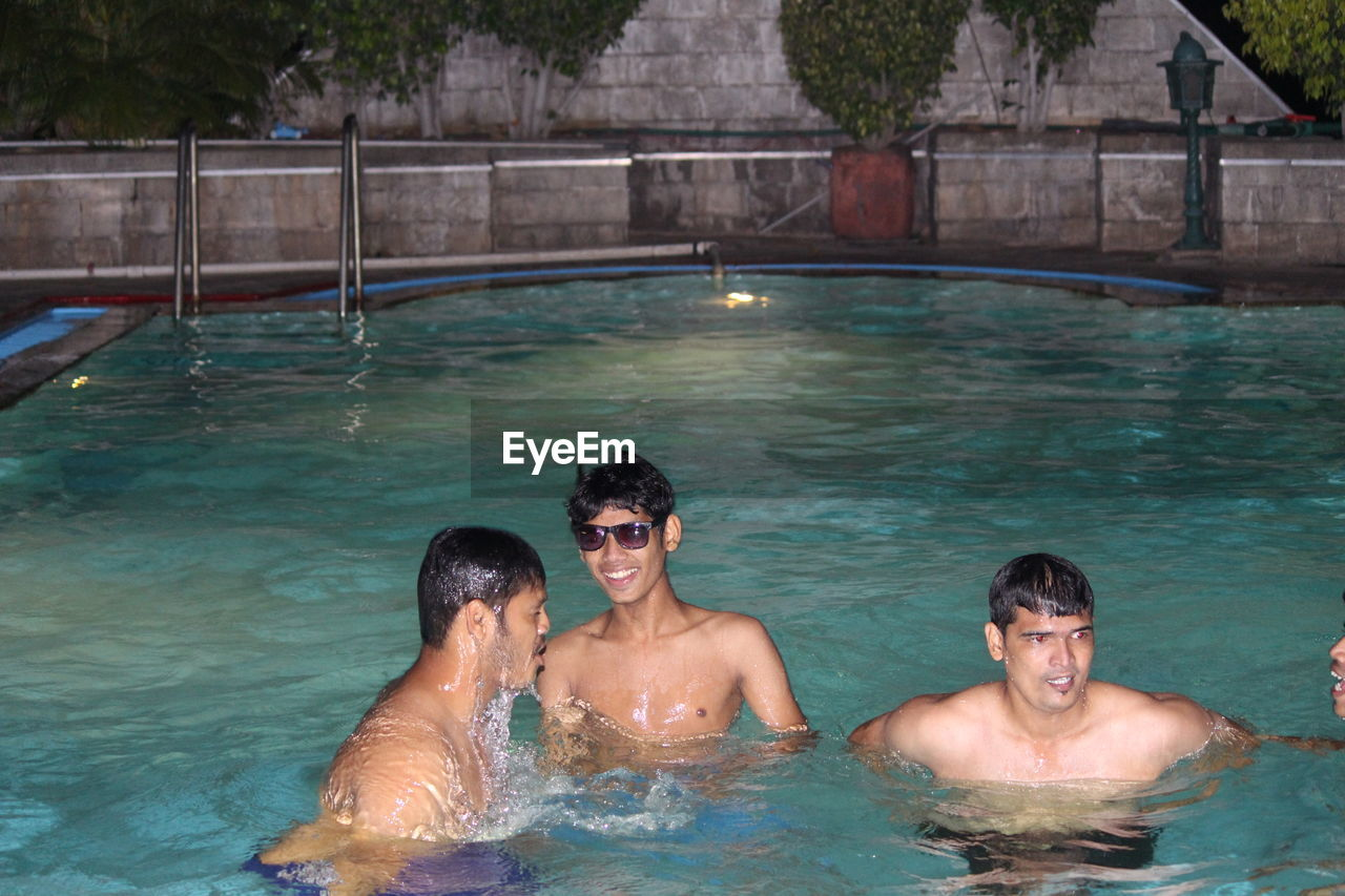 swimming pool, water, vacations, outdoors, smiling, togetherness, day, leisure activity, enjoyment, real people, happiness, swimming, men, adults only, adult, people