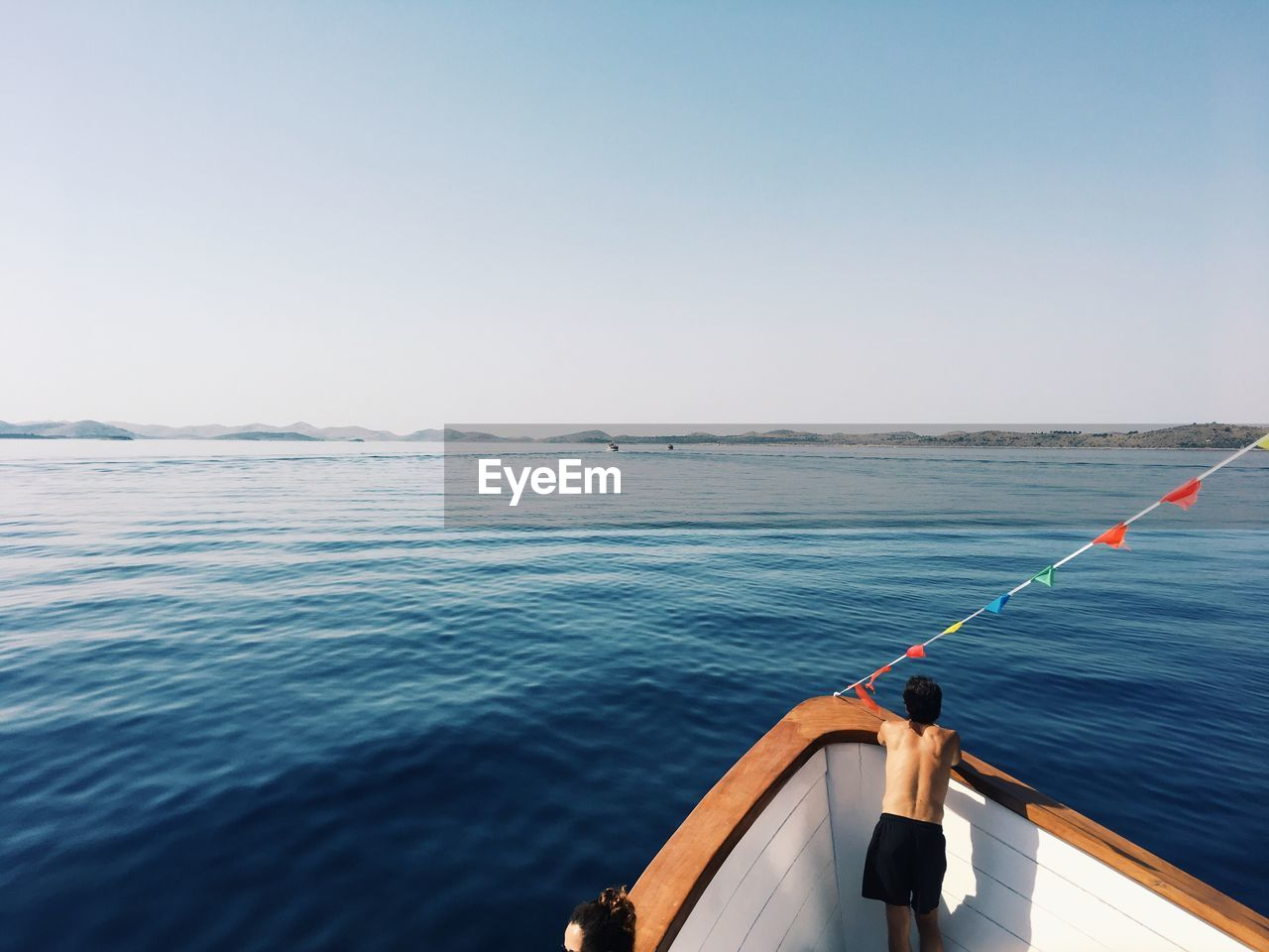 Rear View Of Shirtless Man Standing In Boat On Sea Against Clear Sky