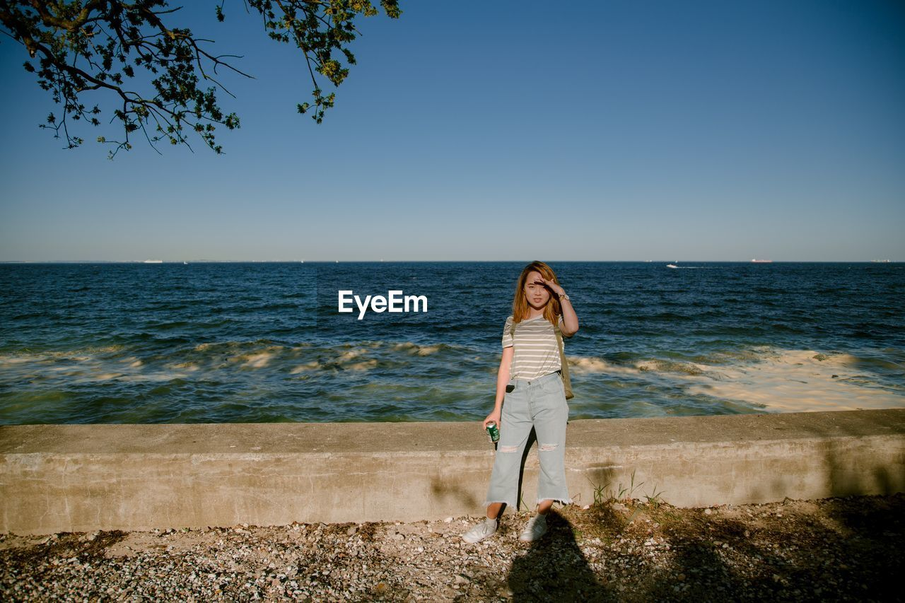 sky, sea, water, one person, beauty in nature, scenics - nature, real people, leisure activity, standing, horizon over water, horizon, lifestyles, casual clothing, land, nature, full length, clear sky, young adult, non-urban scene, outdoors