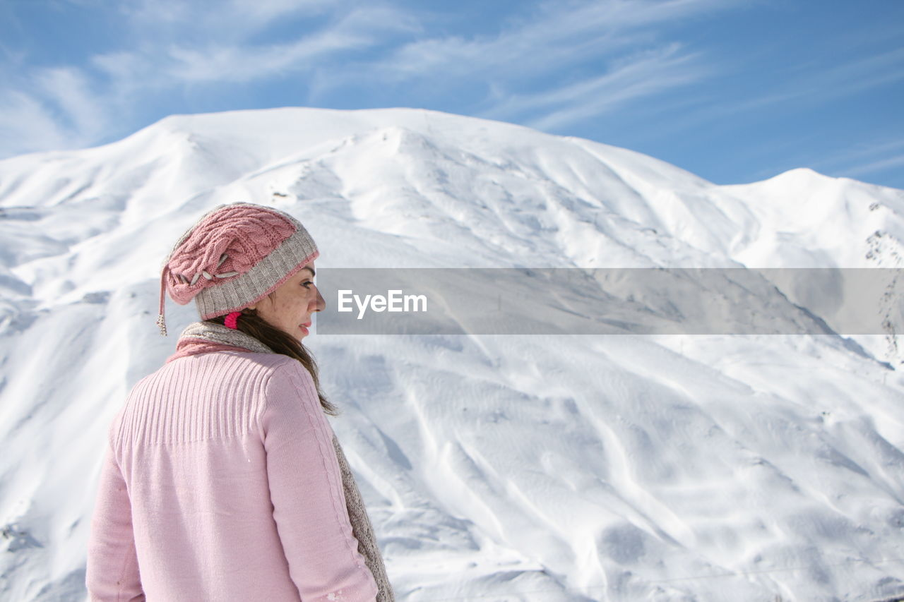Woman in pink sweater standing against snow covered mountain against sky