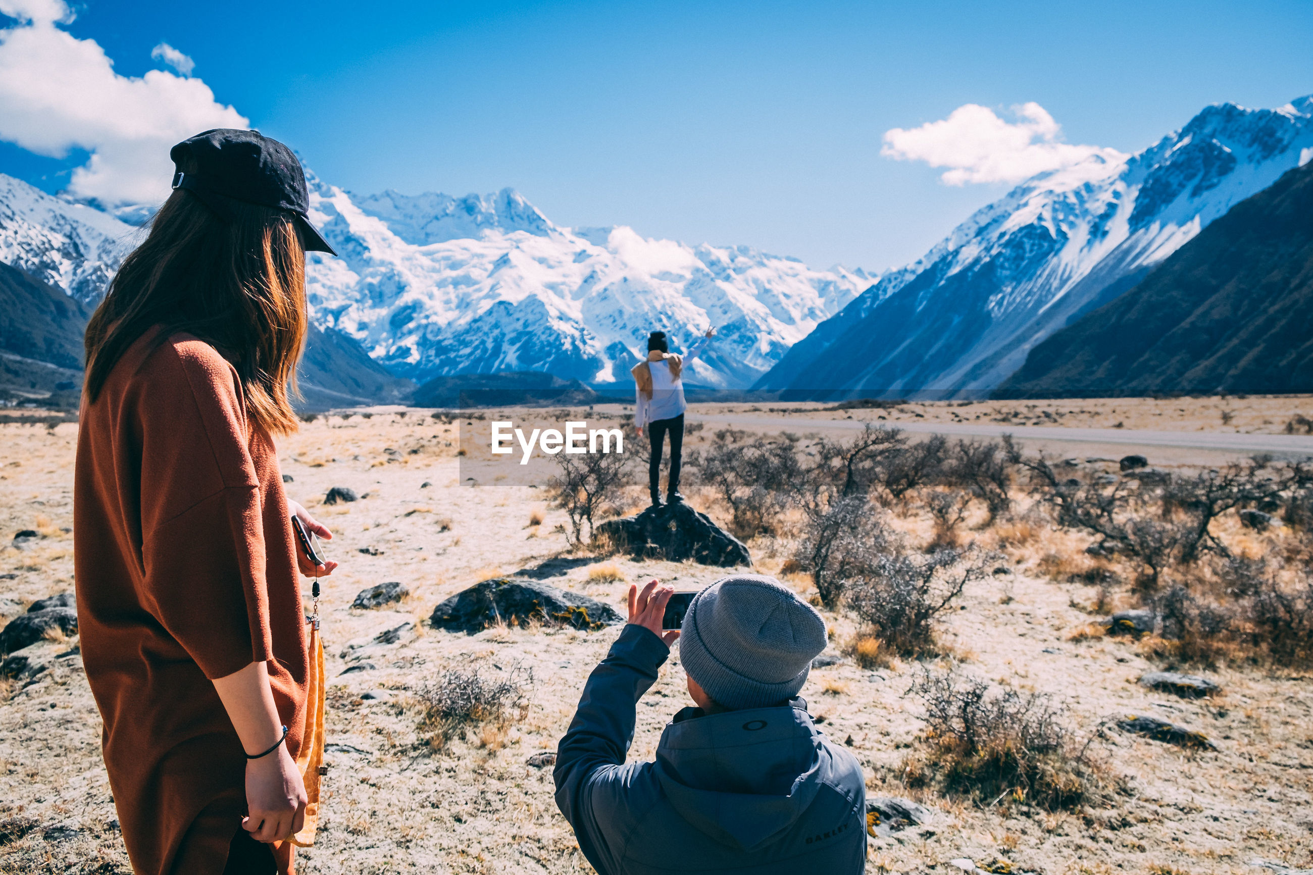 REAR VIEW OF WOMAN PHOTOGRAPHING ON SNOWCAPPED MOUNTAINS