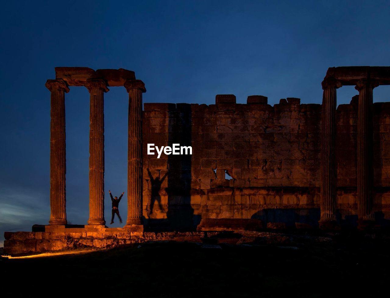Man jumping at old ruins sky at night