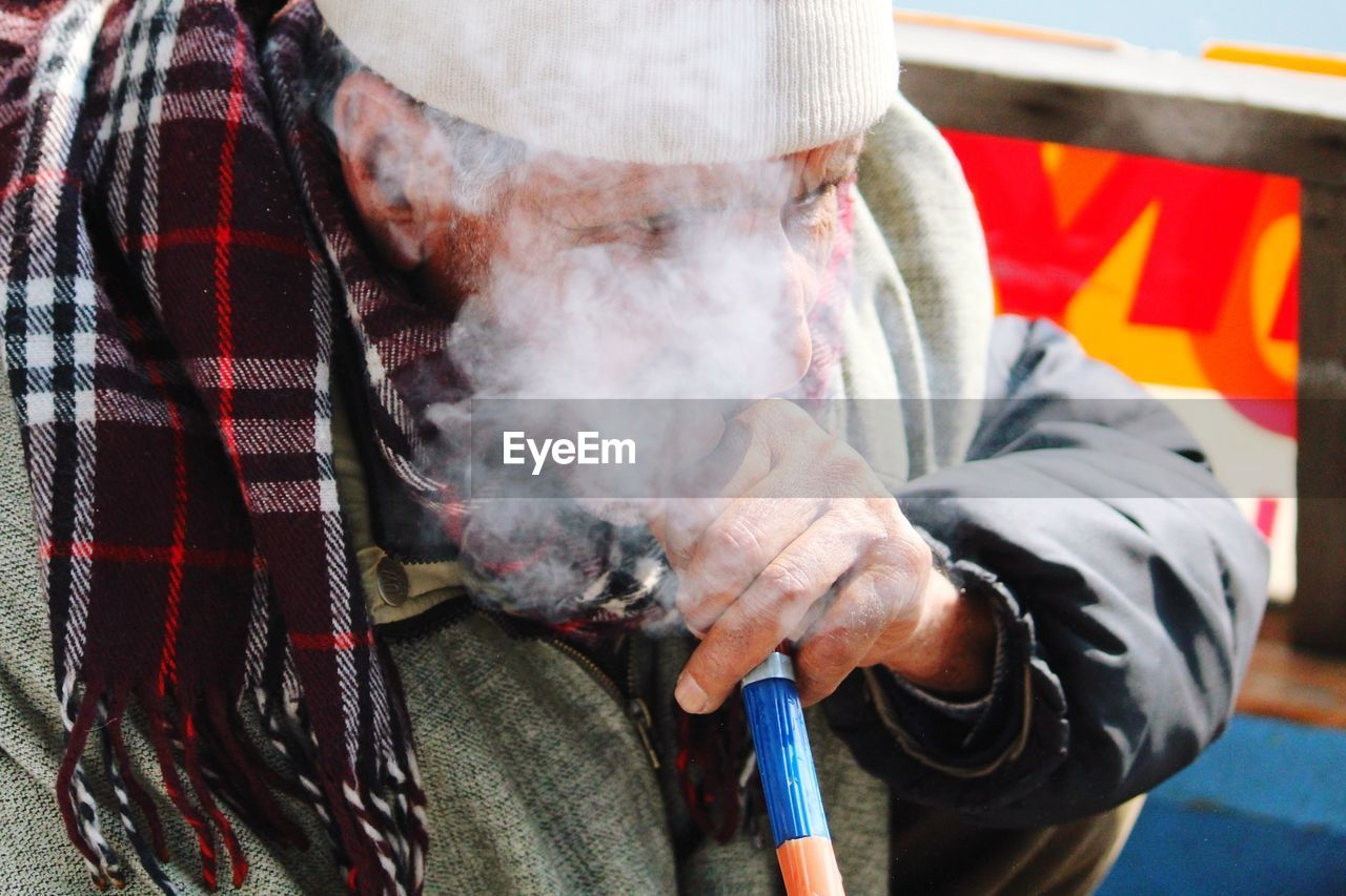 Close-up of man smoking hookah while sitting outdoors