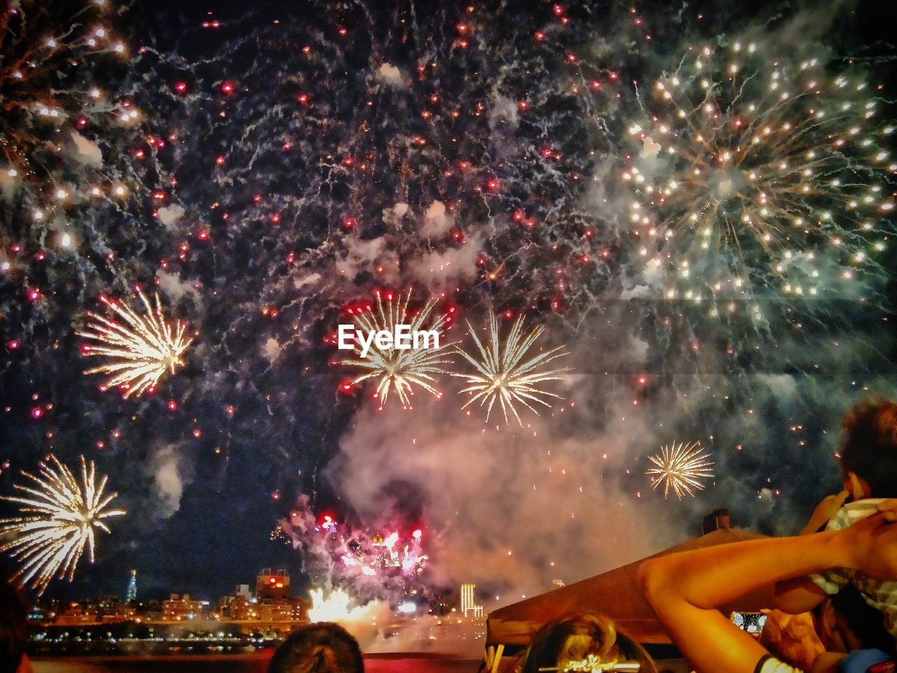 firework display, celebration, firework - man made object, exploding, night, sparks, event, long exposure, arts culture and entertainment, smoke - physical structure, glowing, motion, firework, celebration event, low angle view, multi colored, outdoors, sky, illuminated, no people
