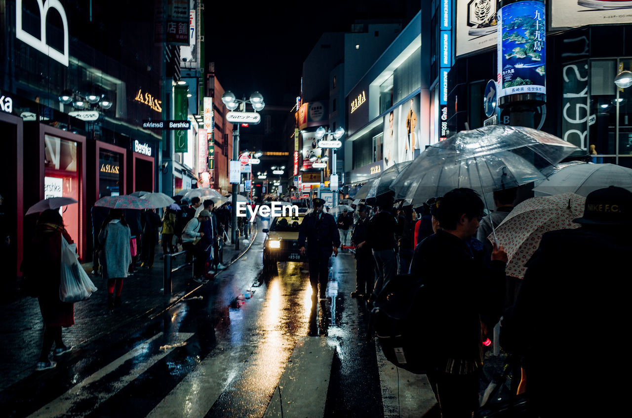 PEOPLE WALKING ON ILLUMINATED ROAD AT NIGHT