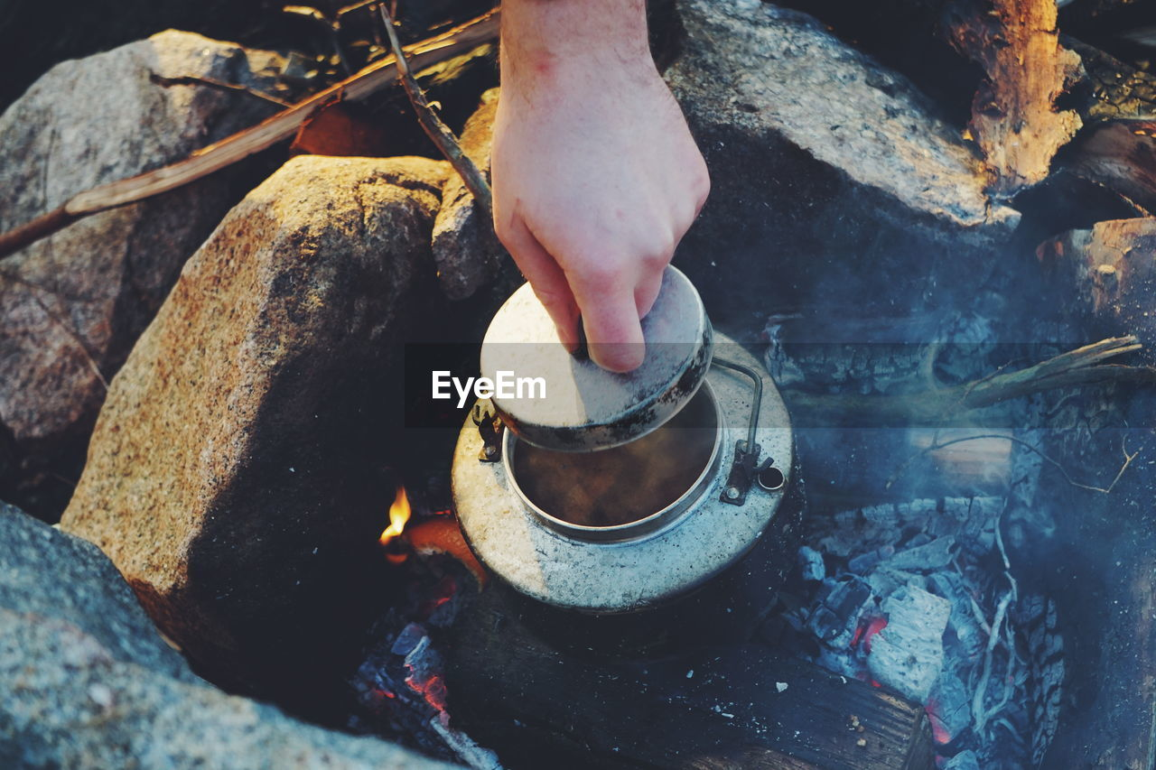 Cropped Hand Holding Lid Of Container On Campfire
