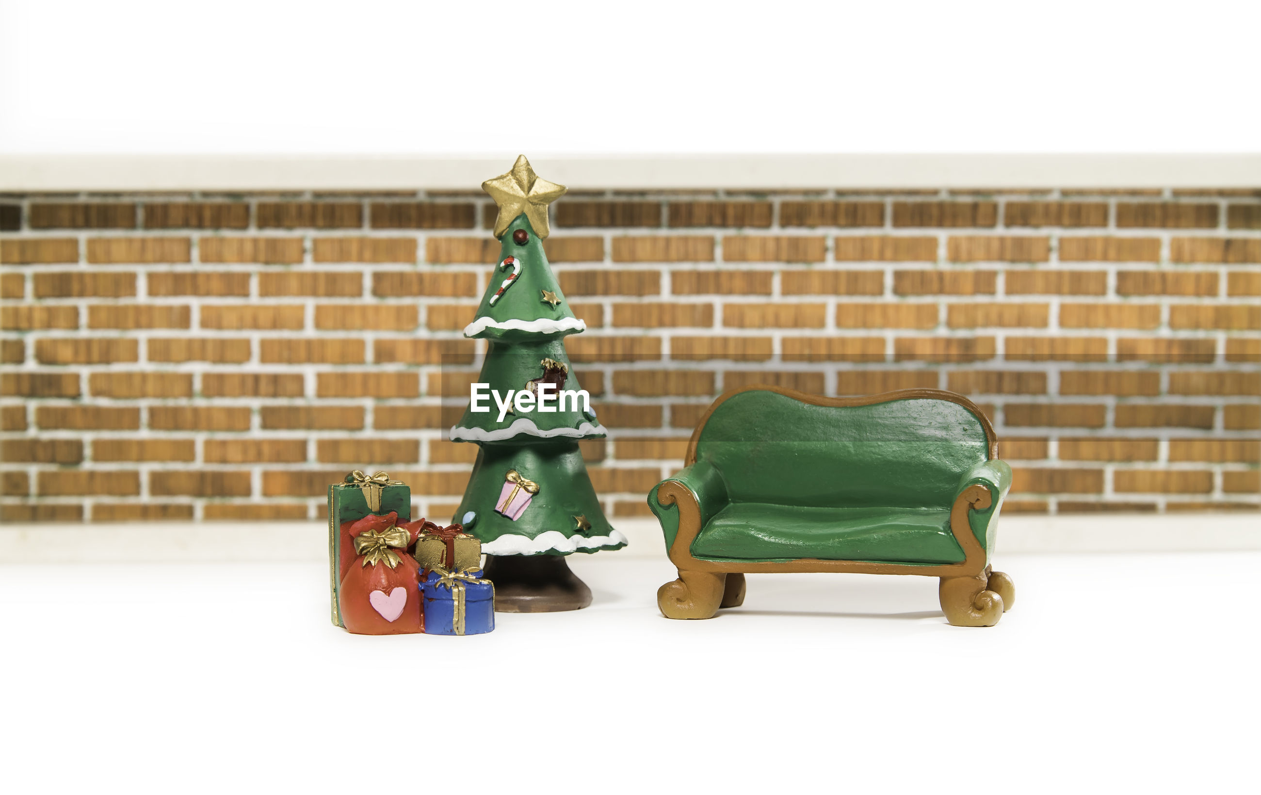 Christmas decoration on table against brick wall