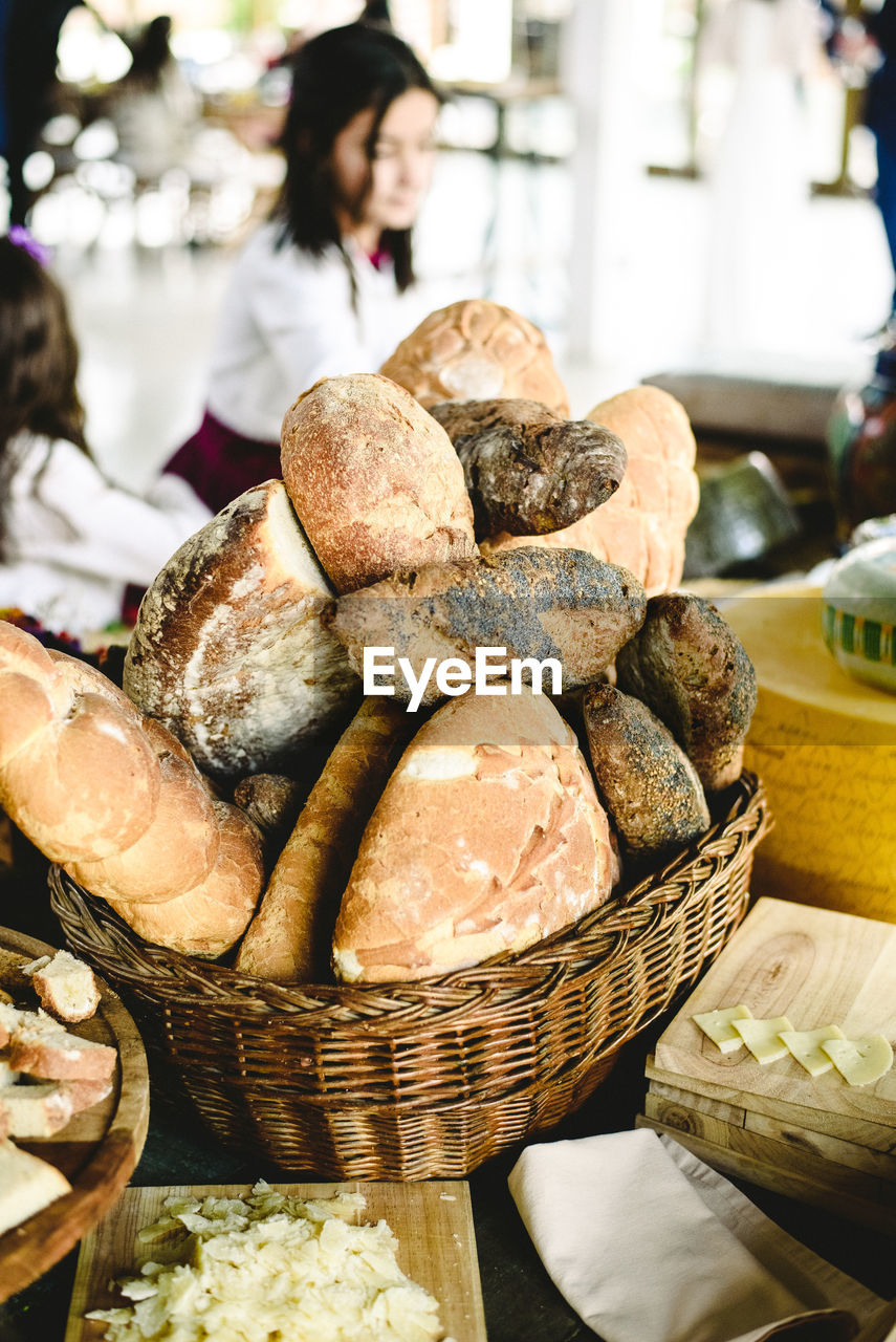 food and drink, food, basket, bread, freshness, container, retail, focus on foreground, wellbeing, incidental people, indoors, loaf of bread, bakery, store, wicker, bun, table, healthy eating, business, choice, french food, brown bread, retail display