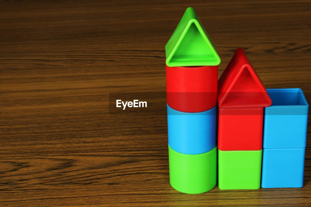HIGH ANGLE VIEW OF MULTI COLORED PLASTIC TOY ON TABLE