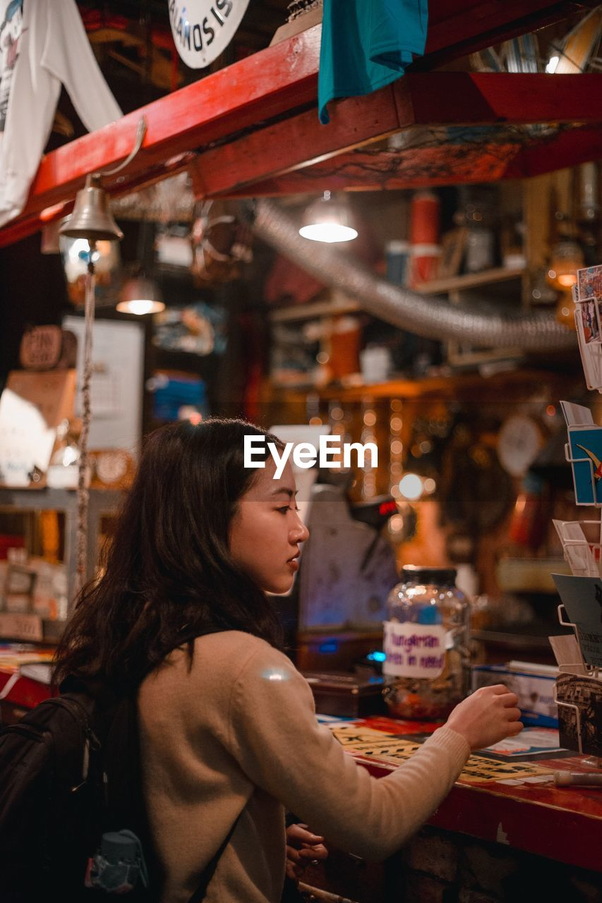 one person, real people, market, retail, choice, leisure activity, women, shopping, store, lifestyles, adult, business, focus on foreground, for sale, indoors, side view, market stall, casual clothing, young adult, buying, hairstyle, retail display, consumerism