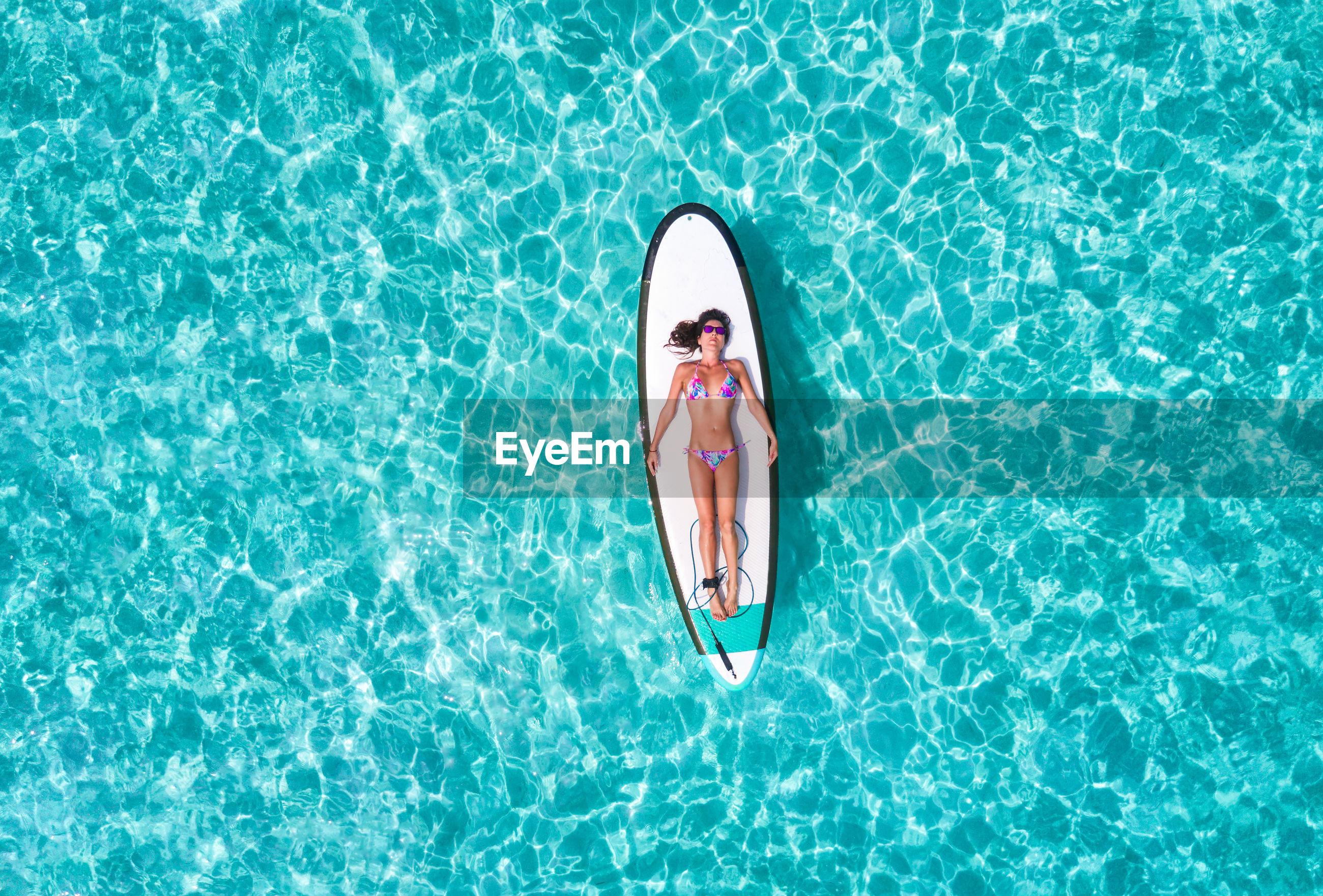Aerial view of woman in bikini lying on surfboard over sea