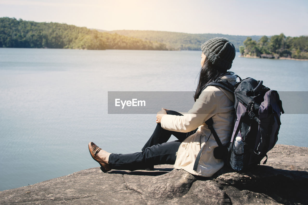 Side view of backpack woman sitting against lake