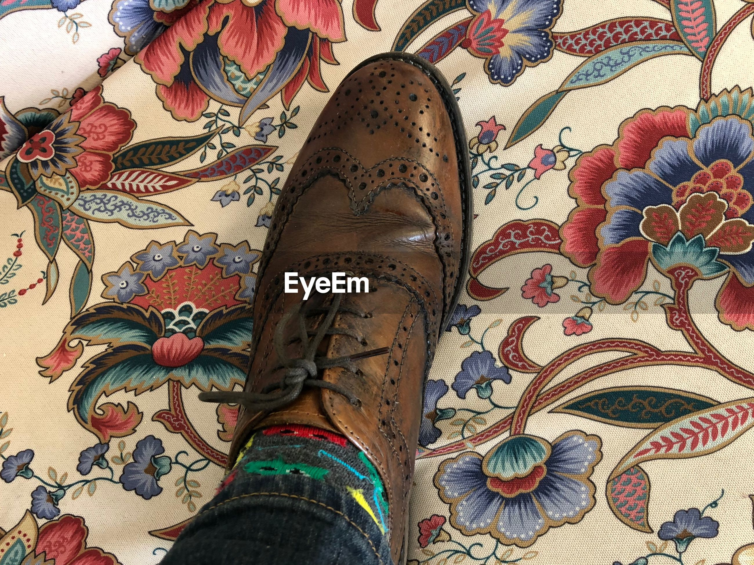 pattern, indoors, body part, floral pattern, multi colored, human leg, human body part, high angle view, low section, design, shoe, art and craft, textile, close-up, one person, adult, tattoo, fashion, limb, choice, human limb, human foot, ornate
