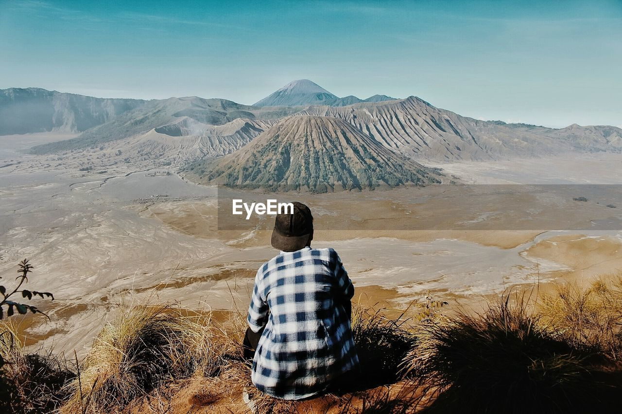 Rear View Of Man Sitting On Volcanic Landscape