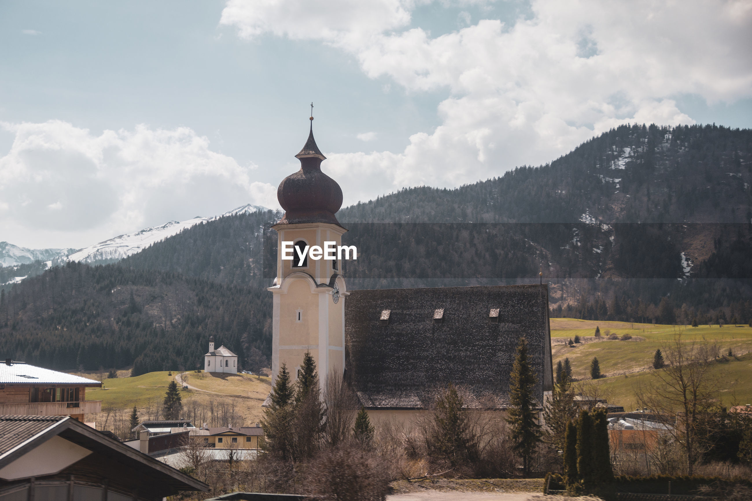 Buildings against sky with mountain in background