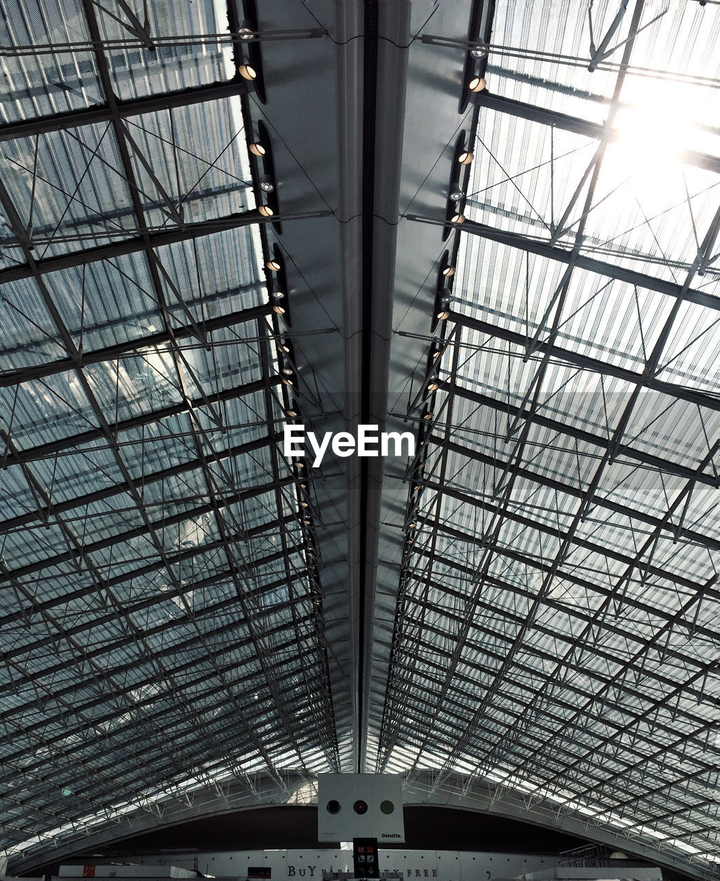 low angle view, ceiling, indoors, pattern, architecture, built structure, no people, metal, modern, sunlight, day, glass - material, design, transportation, architectural feature, skylight, mode of transportation, backgrounds, symmetry