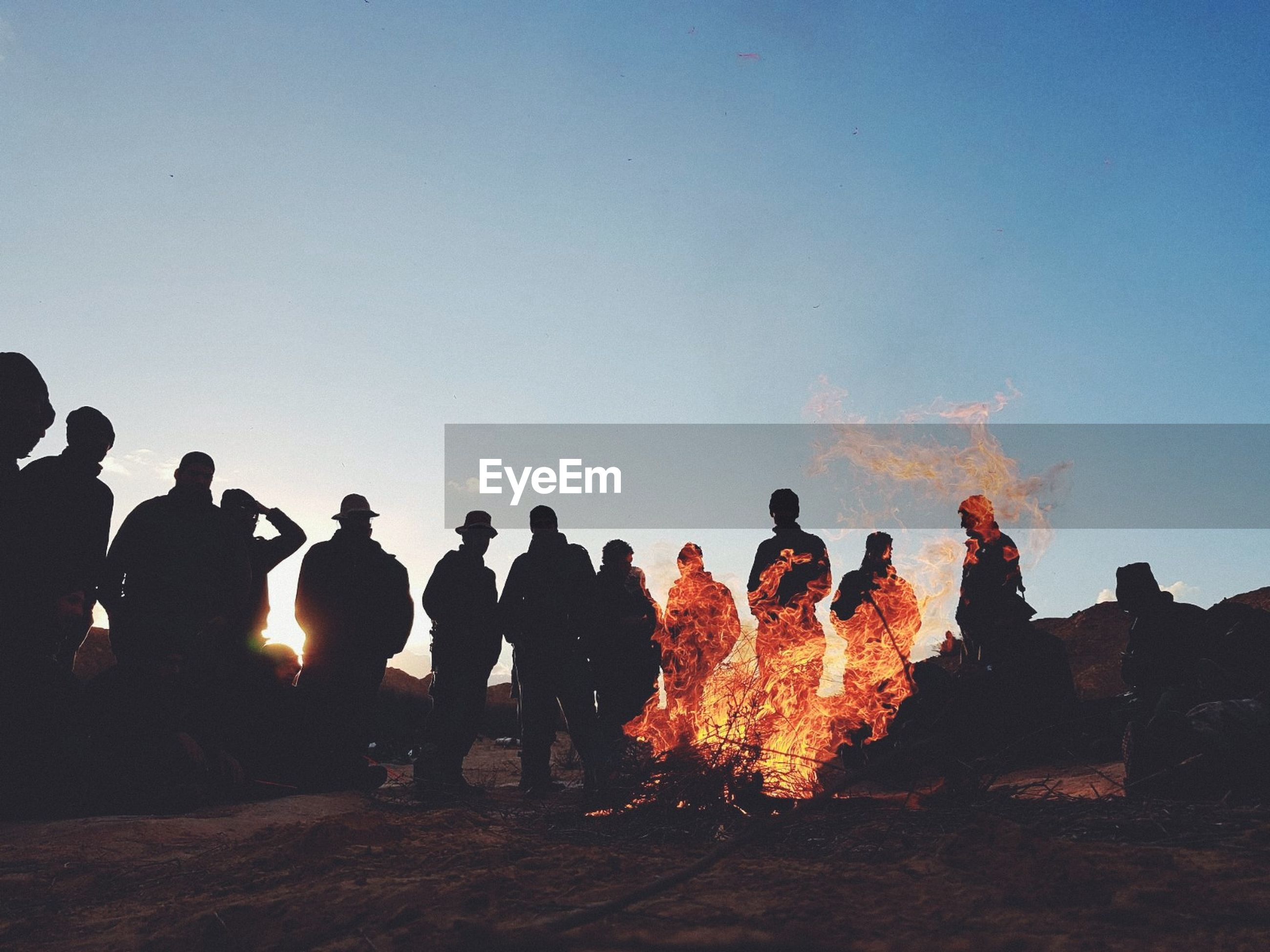 real people, burning, large group of people, flame, men, heat - temperature, bonfire, smoke - physical structure, sky, outdoors, clear sky, leisure activity, women, togetherness, standing, lifestyles, nature, day, people