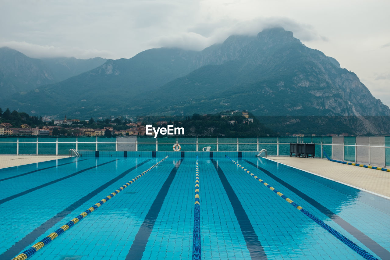 Swimming pool by lake against cloudy sky