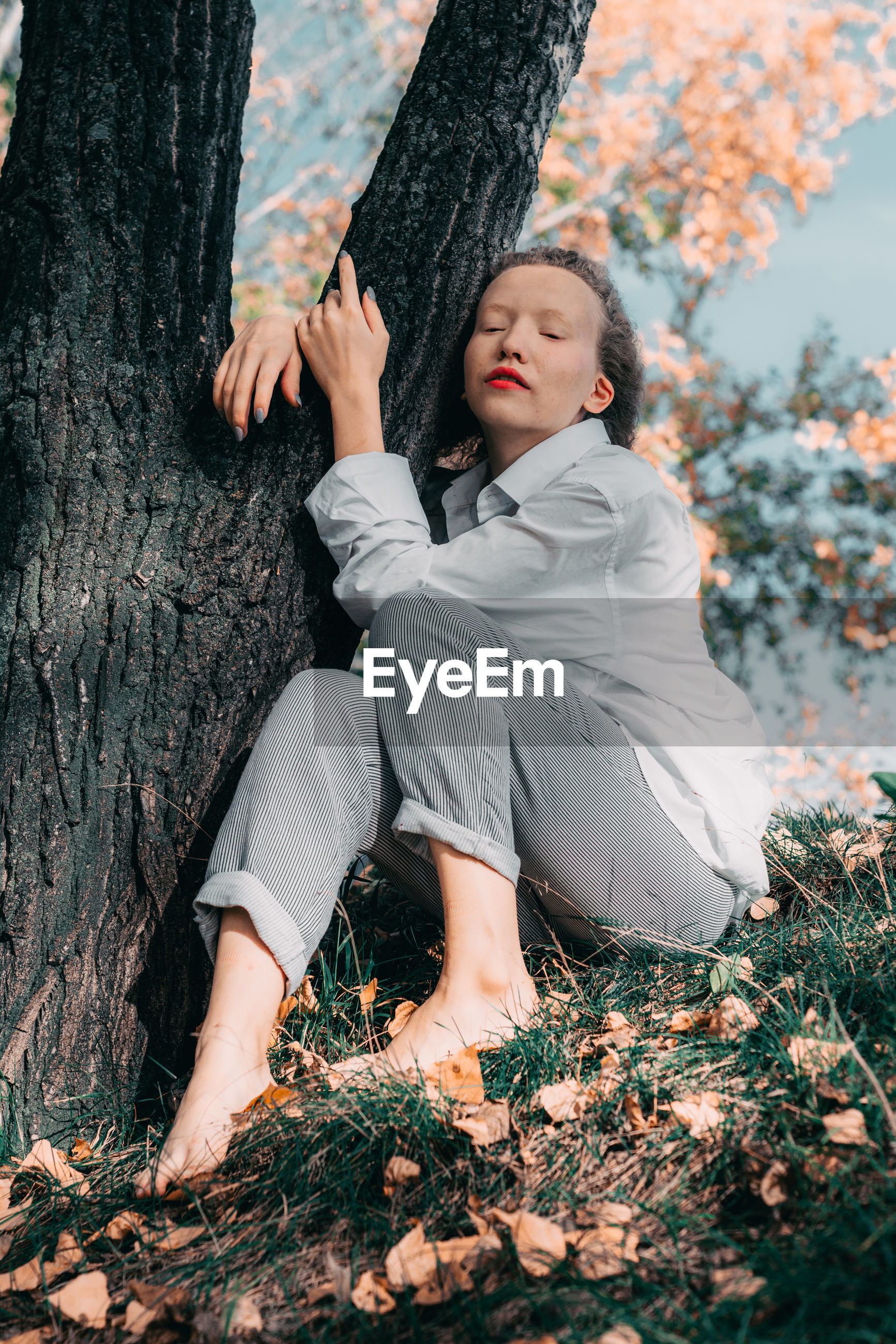 Woman sitting on grass by tree trunk during autumn