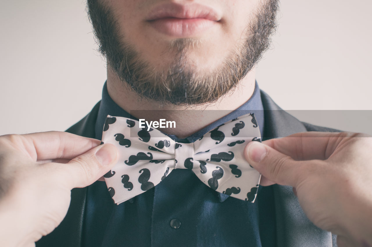 Close-Up Of Young Man Tying Bow Tie