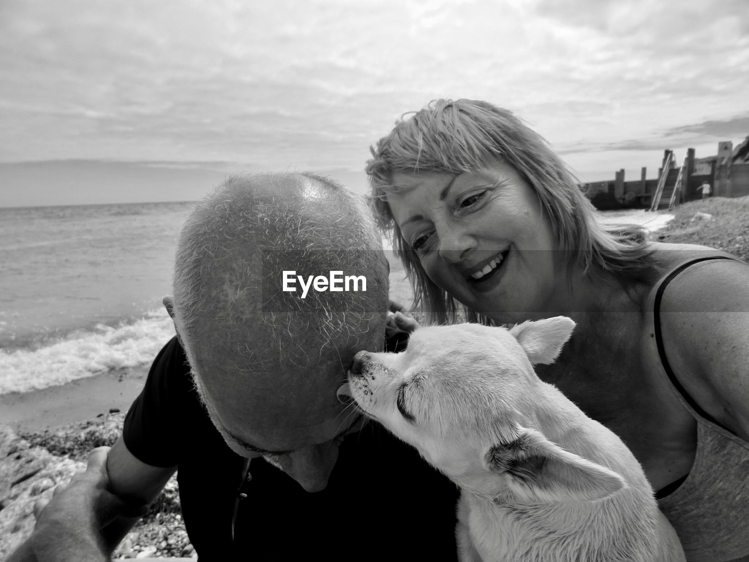 Mature couple with dog at shore of beach
