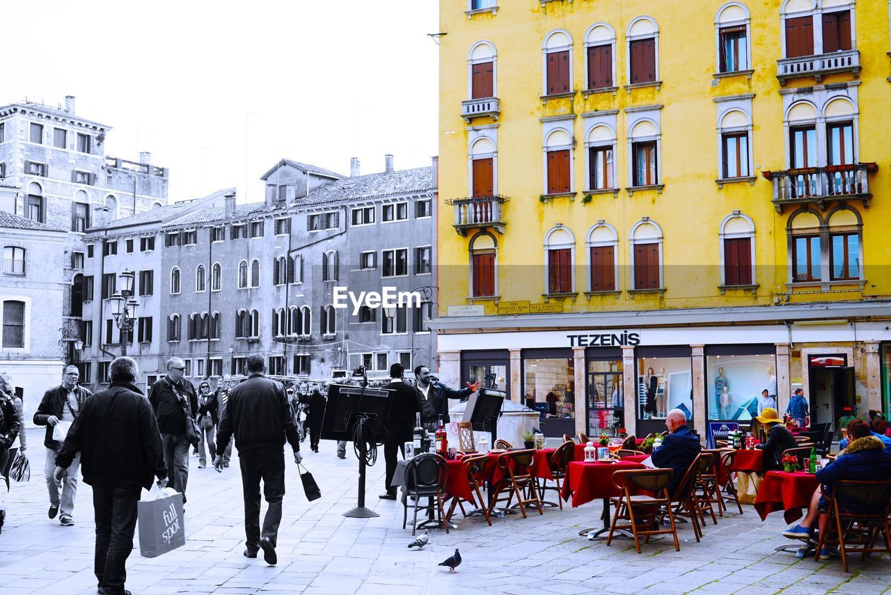 building exterior, architecture, built structure, chair, city, table, street, city life, sidewalk cafe, men, cafe, real people, outdoors, large group of people, day, people