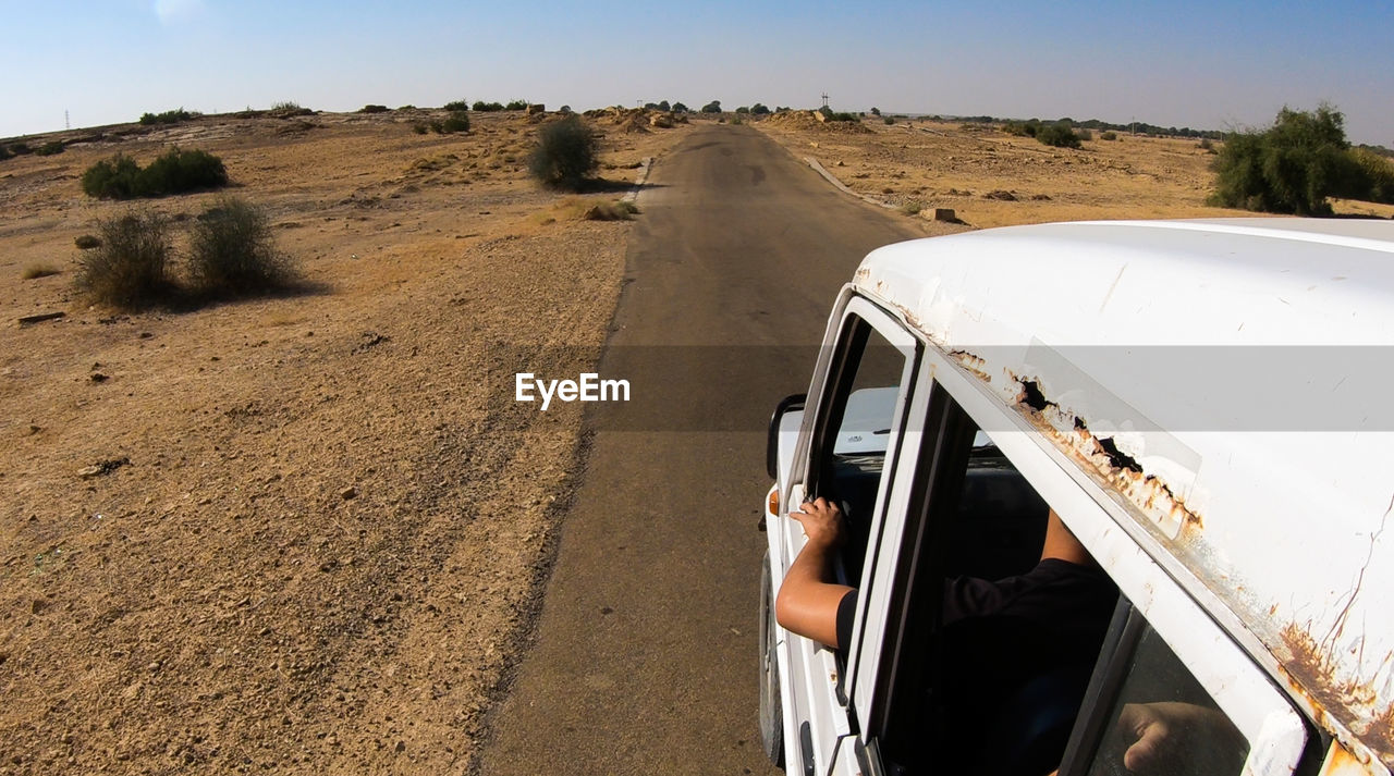 High Angle View Of People In Vehicle On Road Amidst Desert Landscape