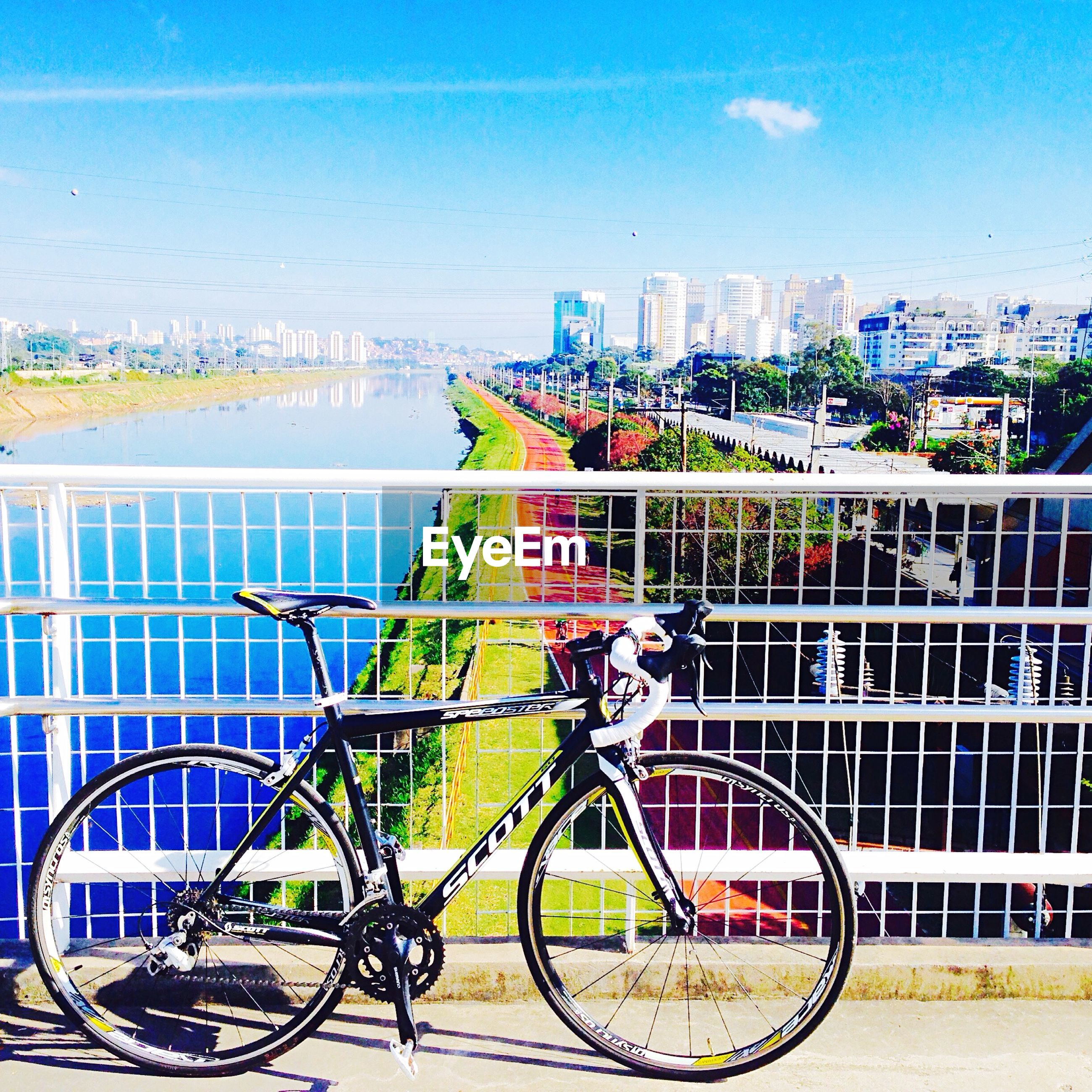 bicycle, transportation, mode of transport, stationary, railing, land vehicle, parking, parked, built structure, architecture, building exterior, sky, water, city, day, blue, outdoors, river, parking lot, no people