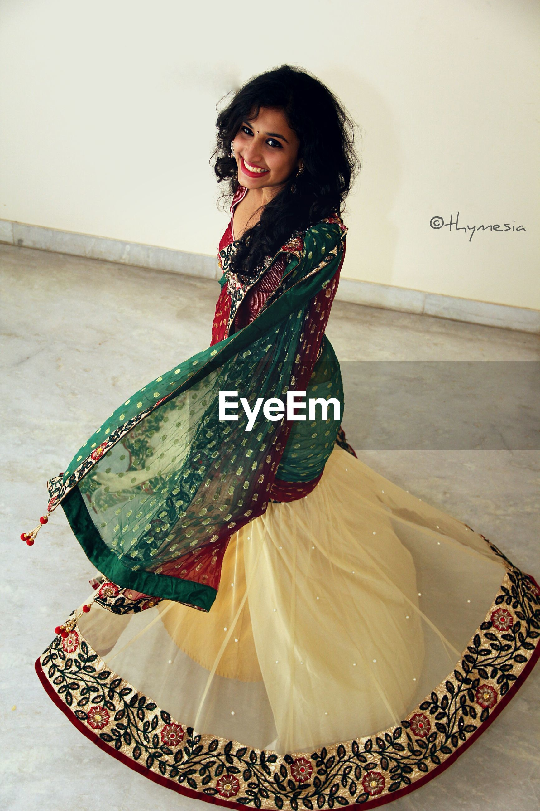 SMILING YOUNG WOMAN STANDING IN TRADITIONAL CLOTHING