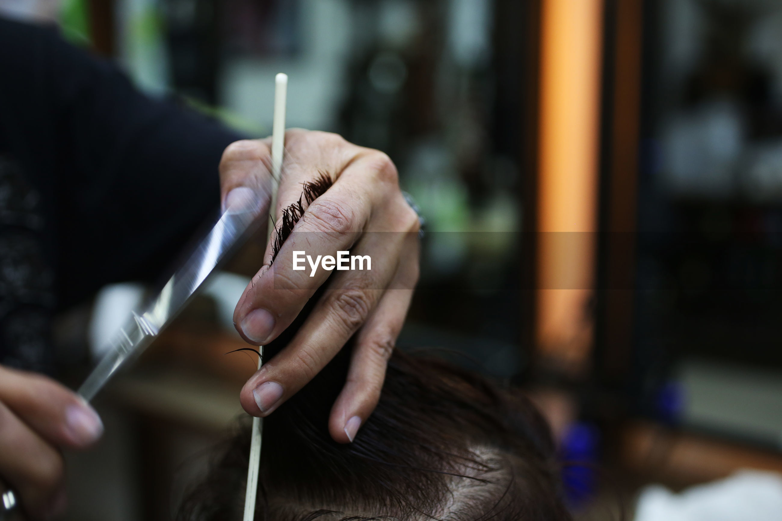 Midsection of barber cutting man hair