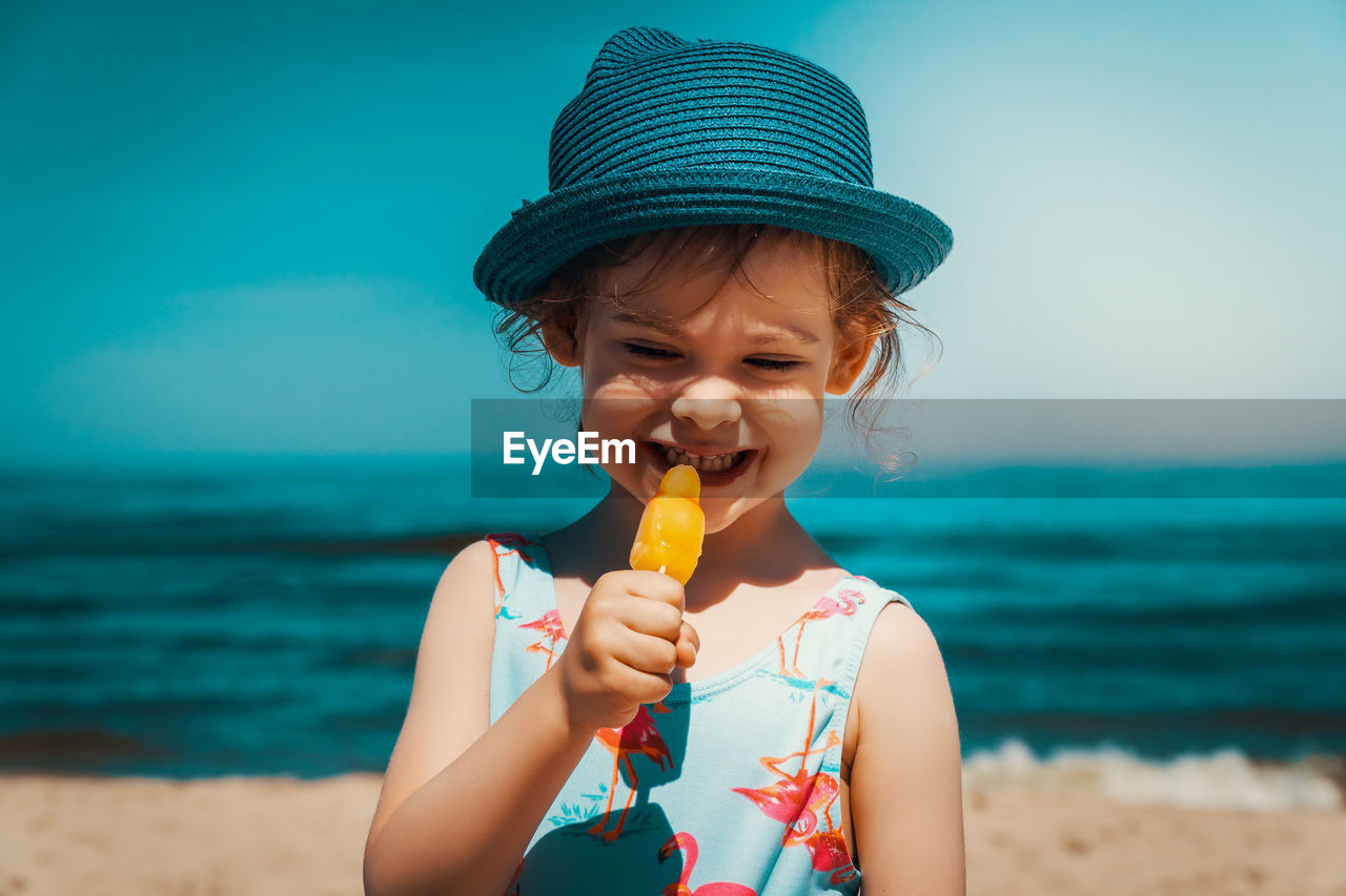 beach, ice cream, sea, front view, land, childhood, sweet food, frozen food, food and drink, real people, sweet, holding, one person, dairy product, child, water, lifestyles, food, eating, day, innocence, outdoors, horizon over water