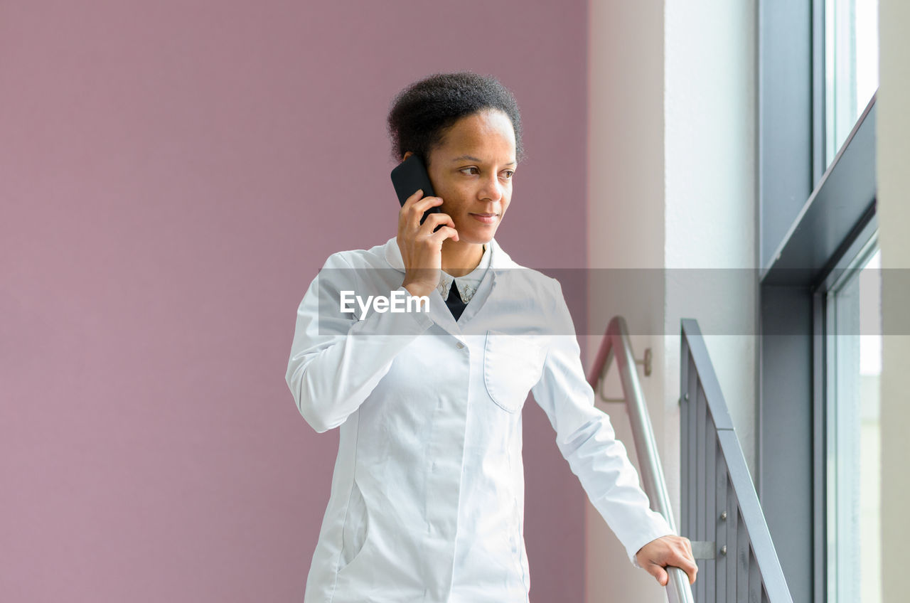 Woman Talking On Mobile Phone While Standing On Steps