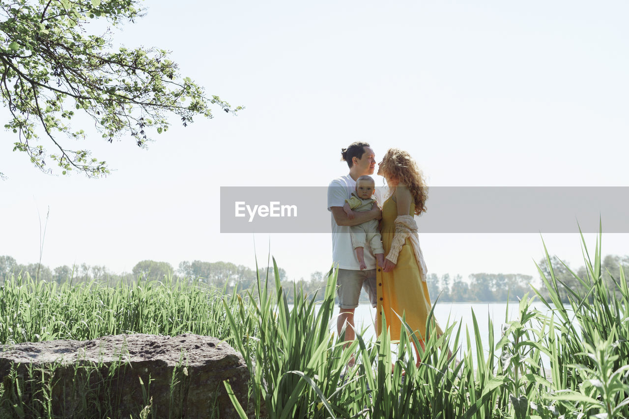 Couple with child standing by plants on land against sky