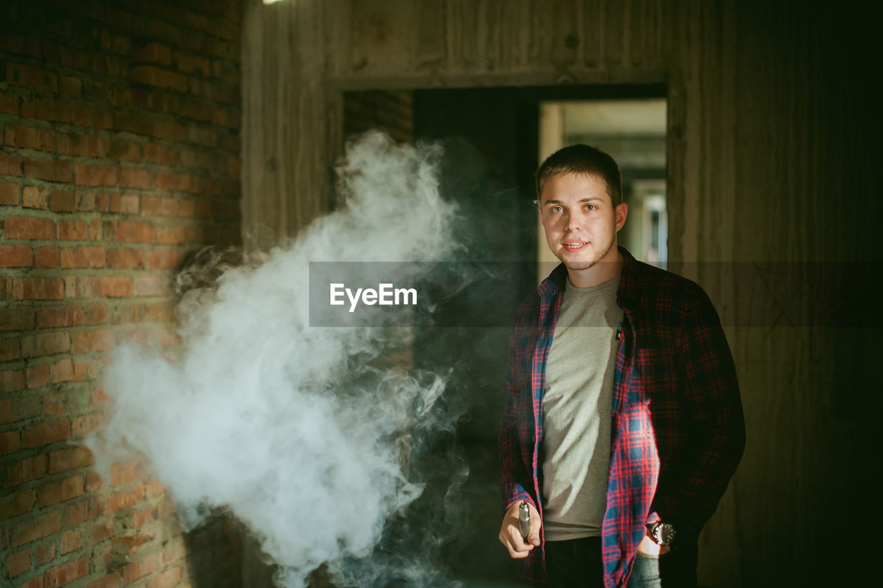 Portrait Of Young Man Smoking Electronic Cigarette