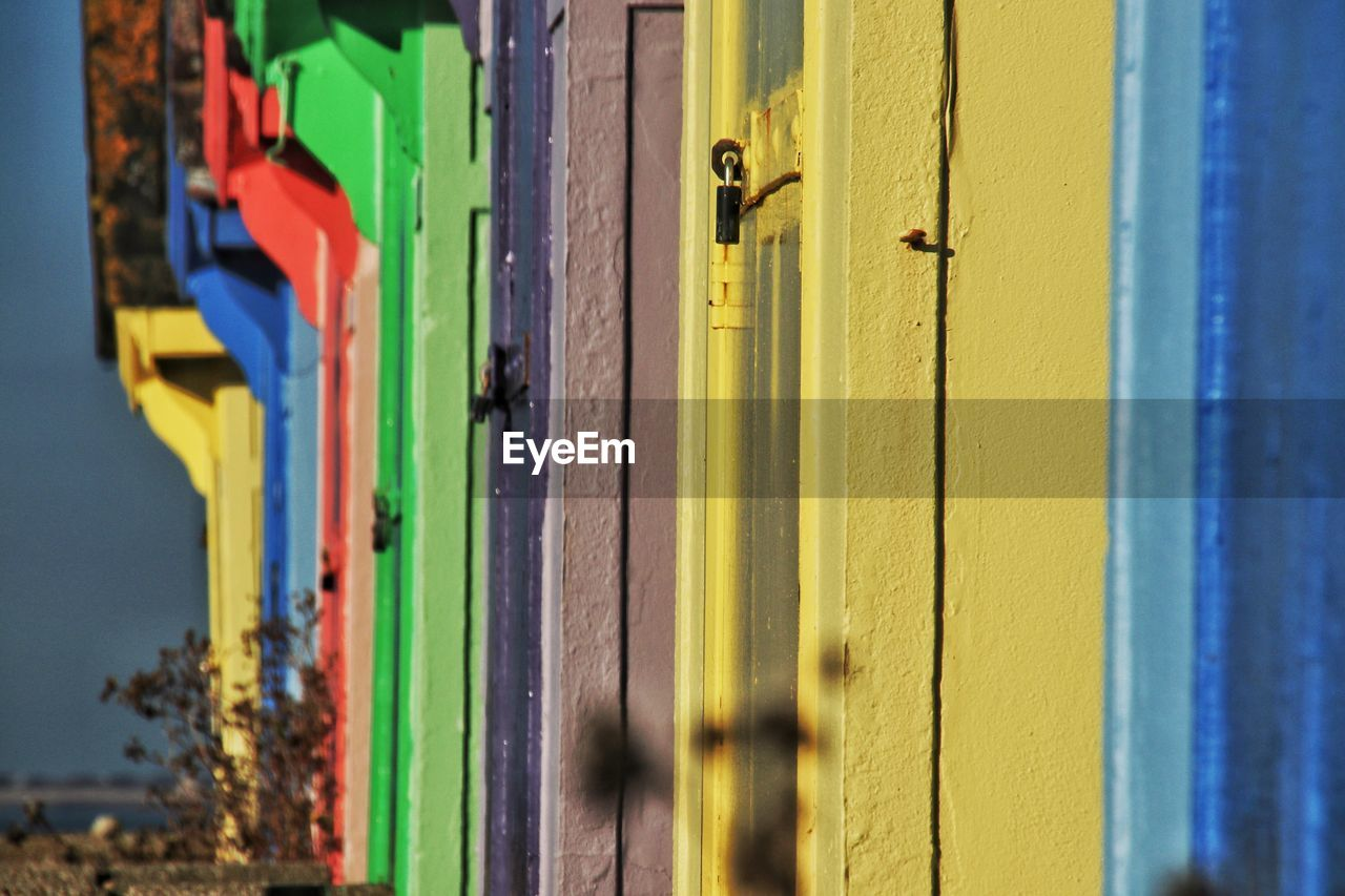 entrance, day, architecture, built structure, building exterior, yellow, door, no people, wood - material, protection, safety, security, multi colored, selective focus, sunlight, metal, building, outdoors, close-up, focus on foreground, latch