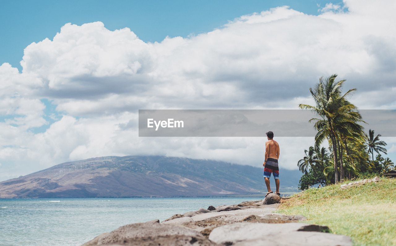 Rear view of shirtless man standing on rock against sky