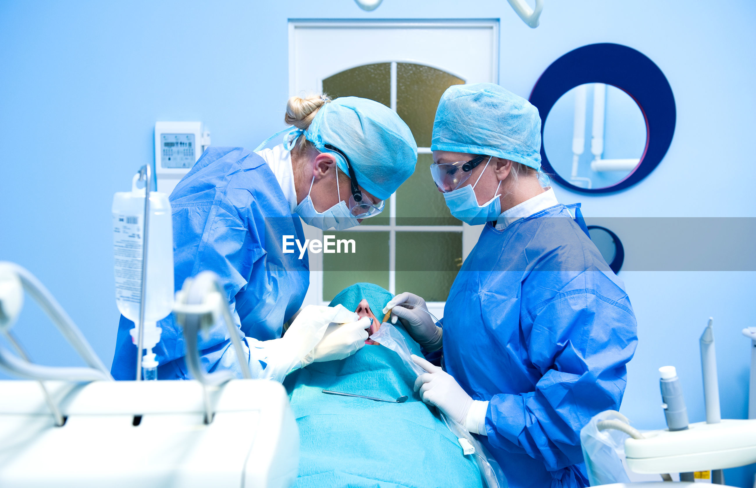 Doctors performing dental implantation in operating room