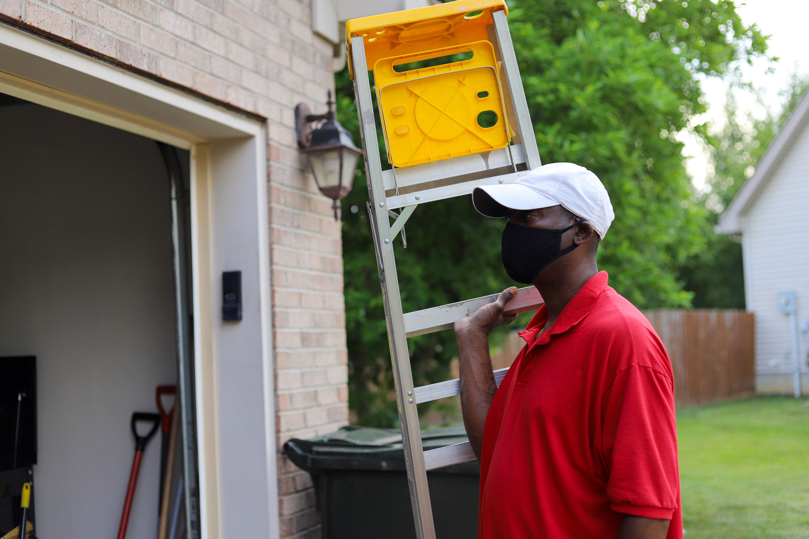A portrait of a african-american man carrying a ladder into a garage and wearing a mask