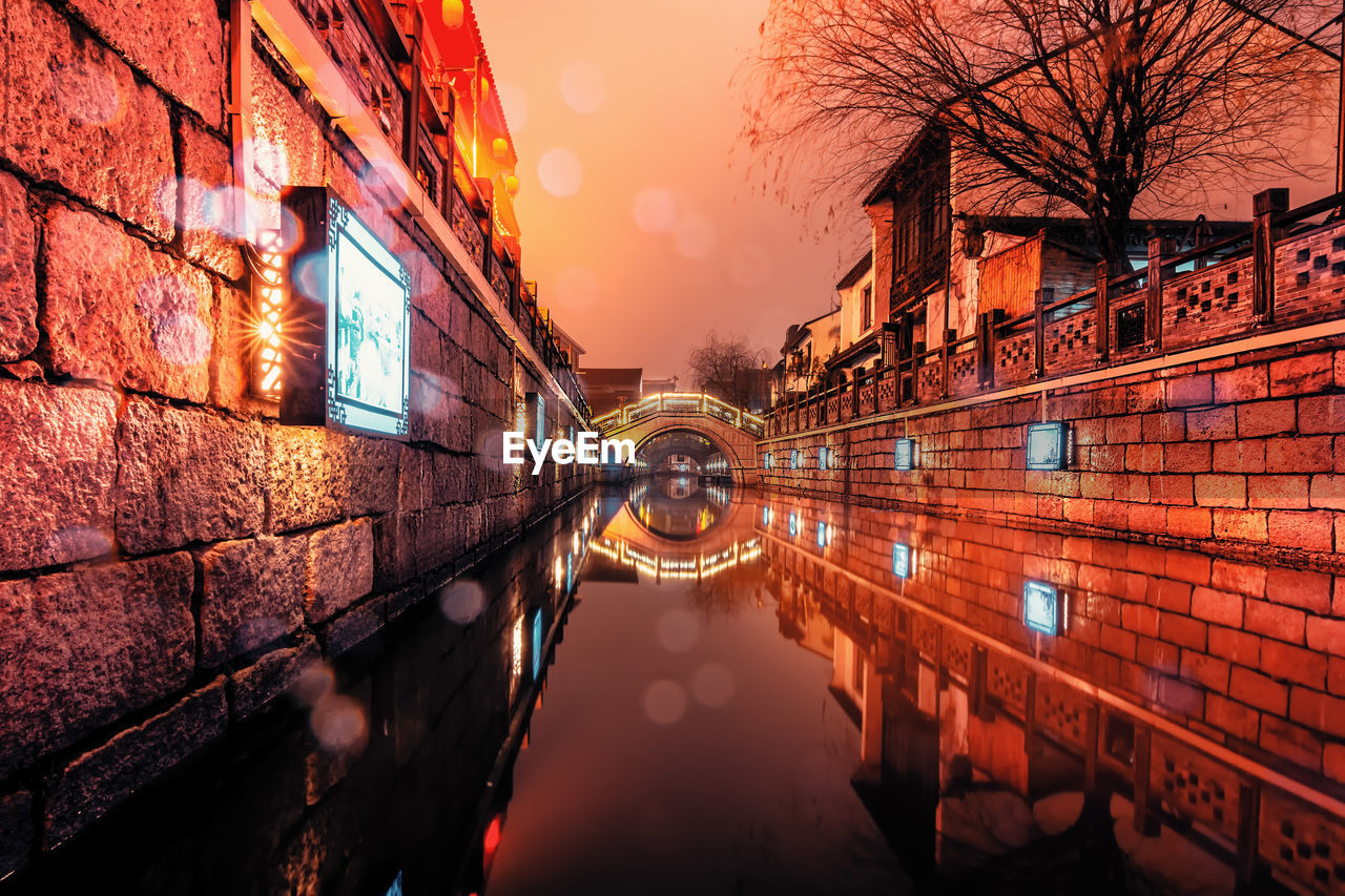 REFLECTION OF ILLUMINATED BUILDING IN CANAL