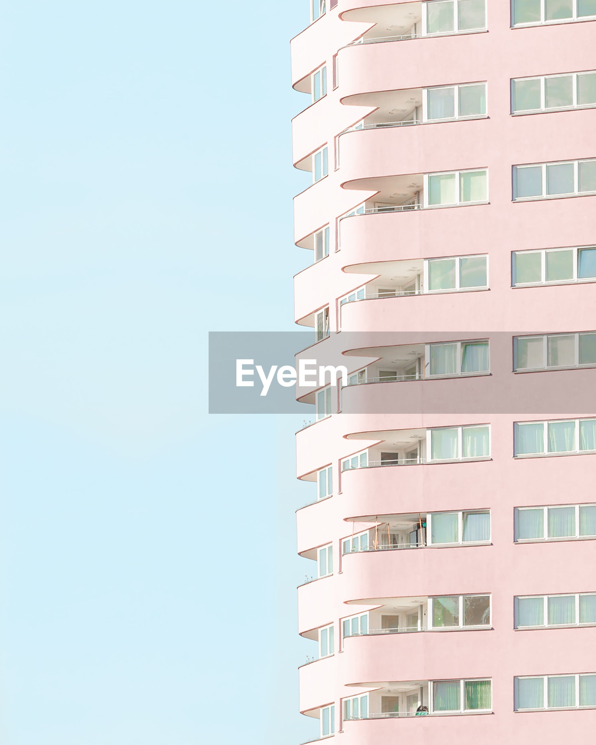 LOW ANGLE VIEW OF APARTMENT BUILDING AGAINST CLEAR SKY