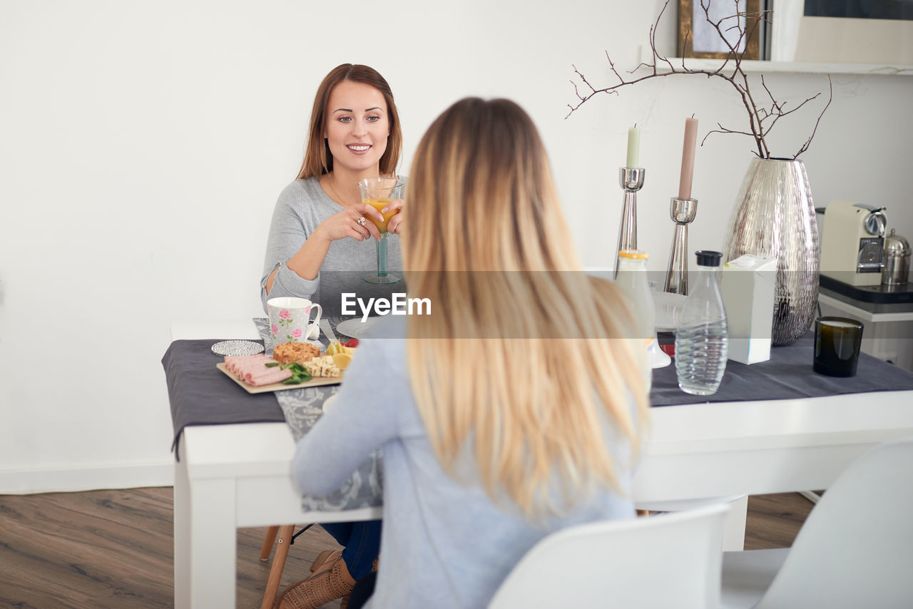 Friends talking while having breakfast at table