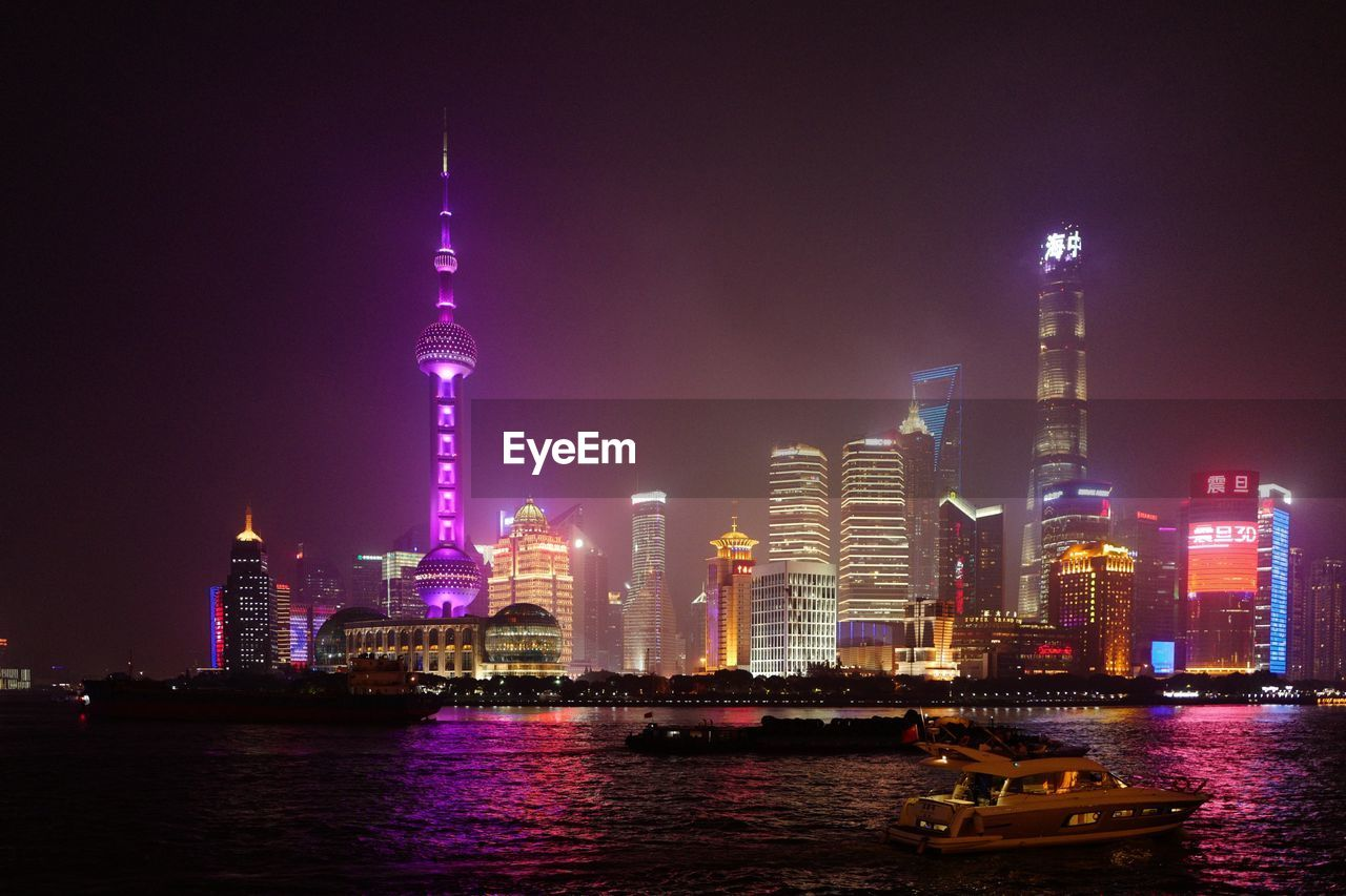 building exterior, architecture, built structure, city, office building exterior, building, tall - high, illuminated, water, skyscraper, night, tower, sky, landscape, waterfront, travel destinations, cityscape, travel, river, modern, no people, outdoors, financial district, spire, purple, passenger craft
