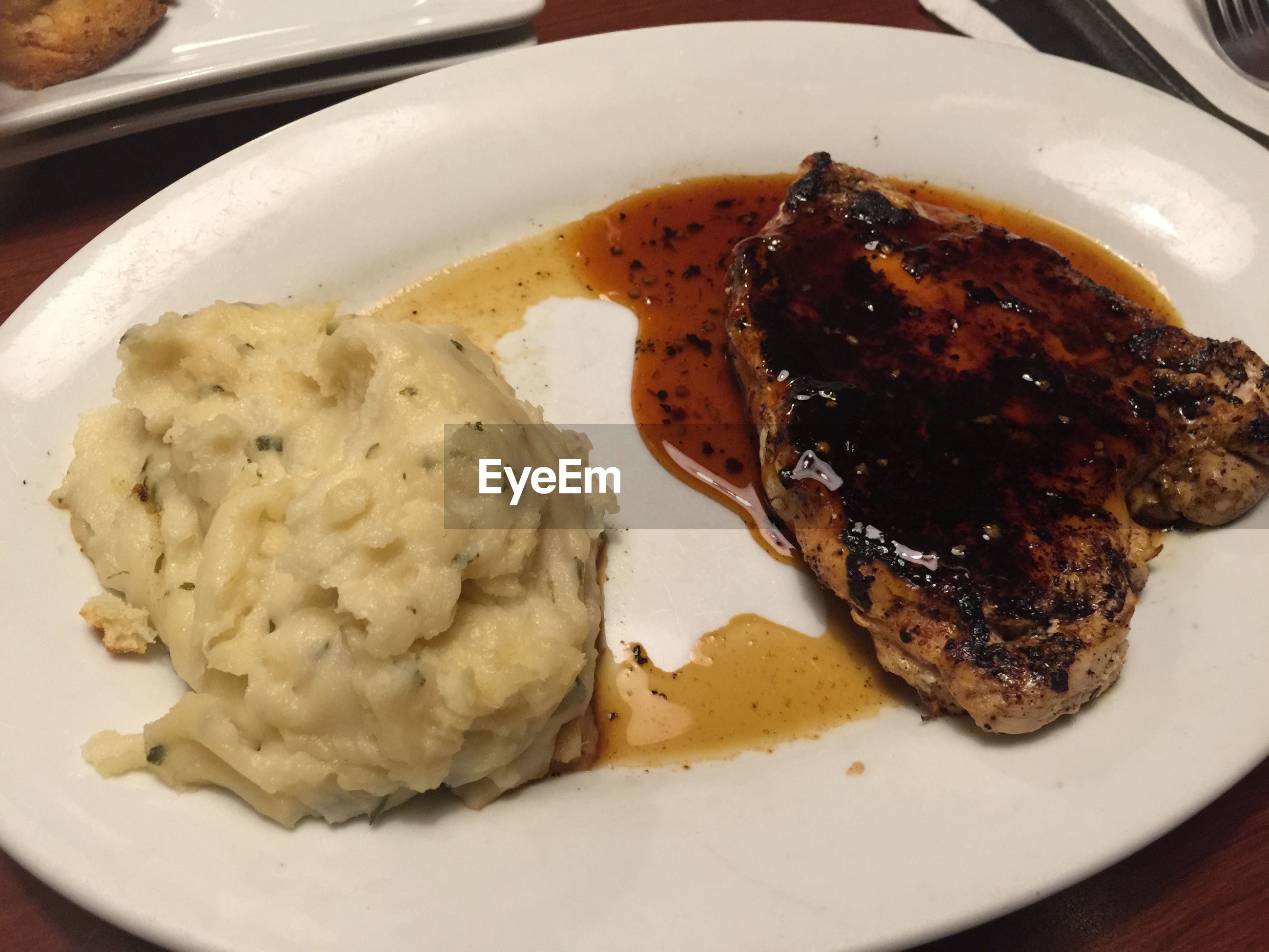 Close-up of mashed potatoes and meat on plate in restaurant