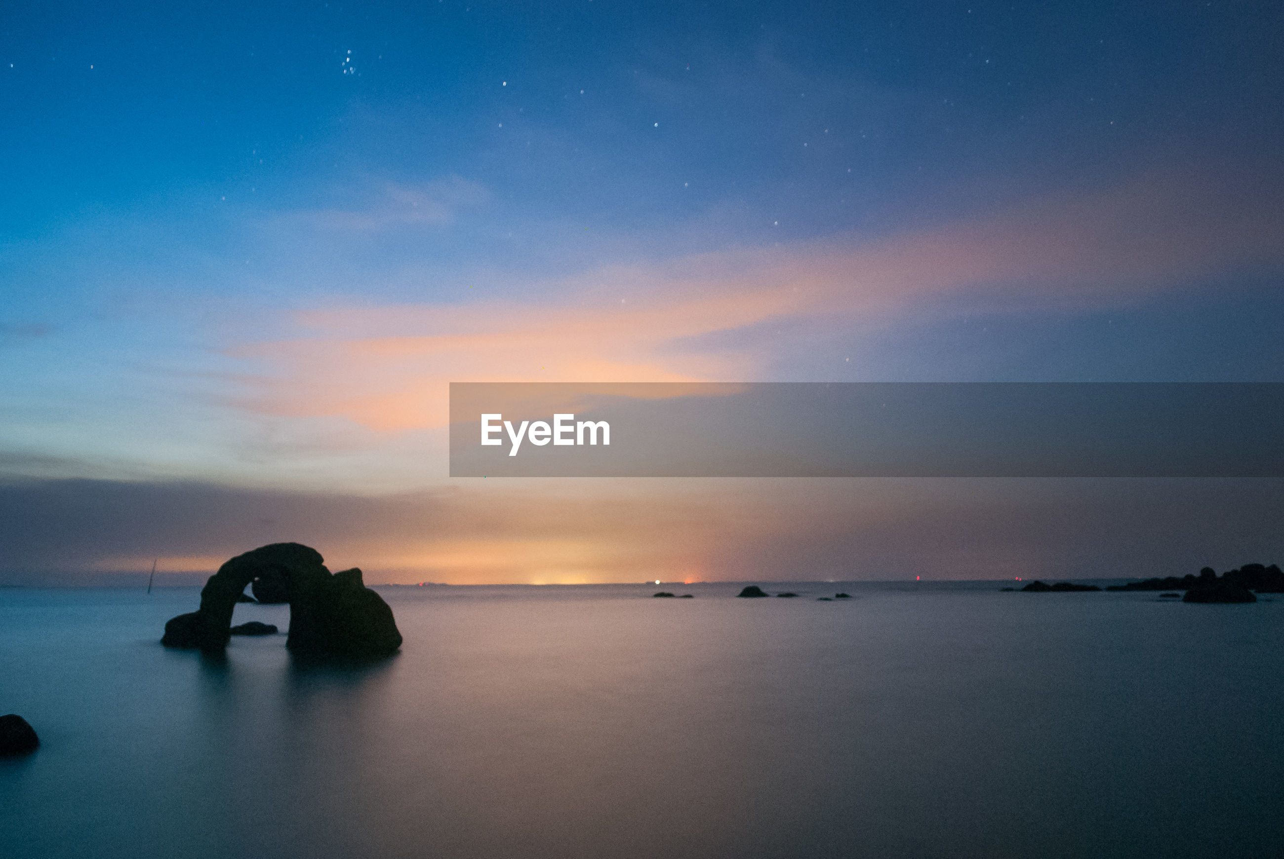Scenic view of seascape against cloudy sky at sunset