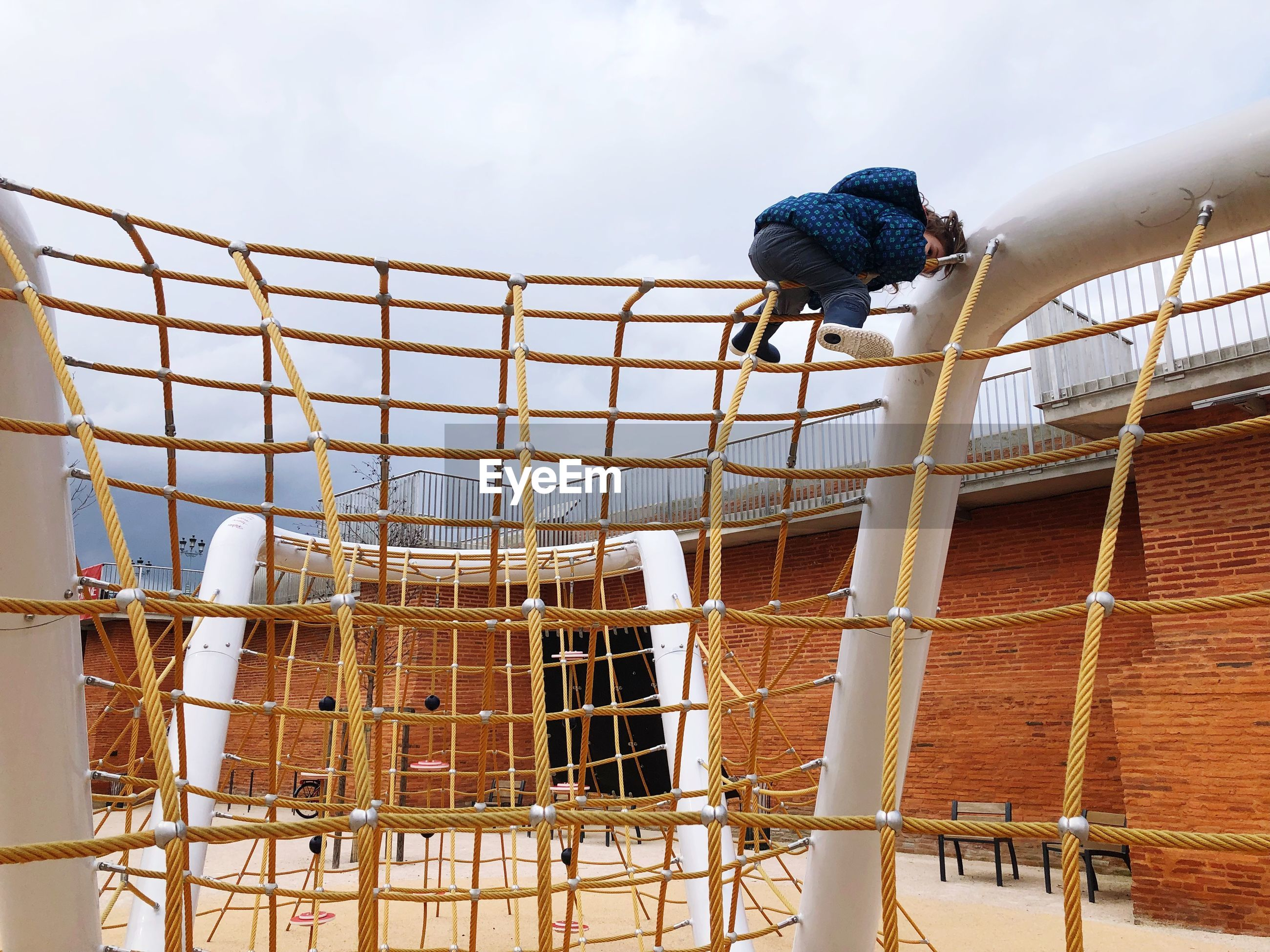 Low angle view of girl playing on outdoor play equipment against cloudy sky