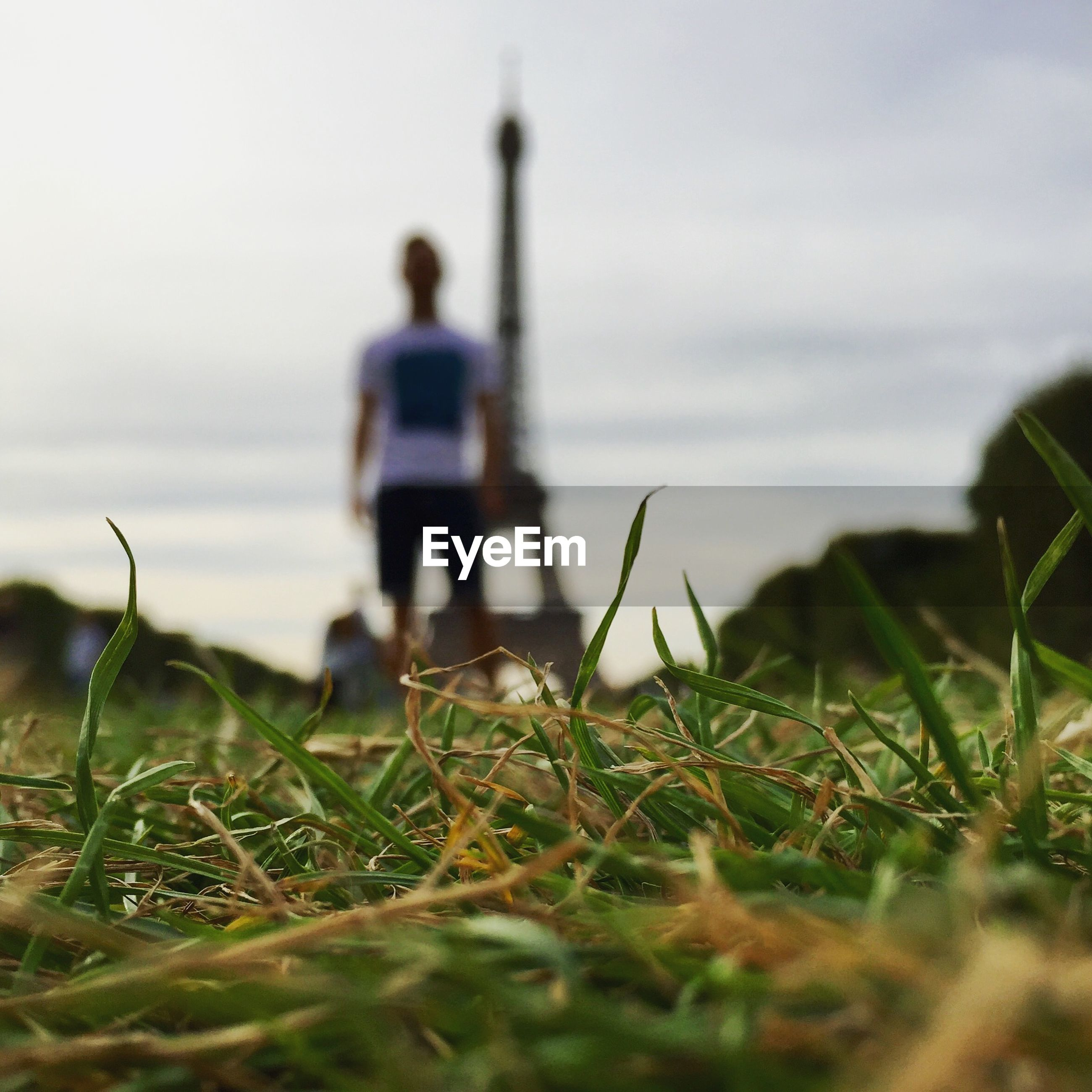Low angle view of man standing on grassy field against eiffel tower