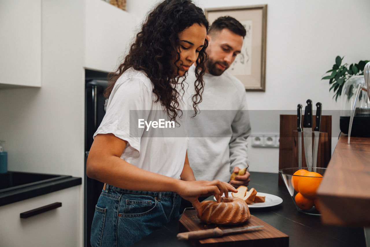 YOUNG COUPLE LOOKING AT FOOD